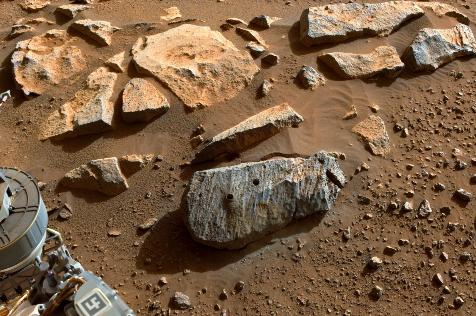 """Two holes where the Perseverance rover's drill obtained chalk-size samples from the rock nicknamed """"Rochette,"""" can be seen on Mars, Sept. 7, 2021. (NASA via AFP)"""