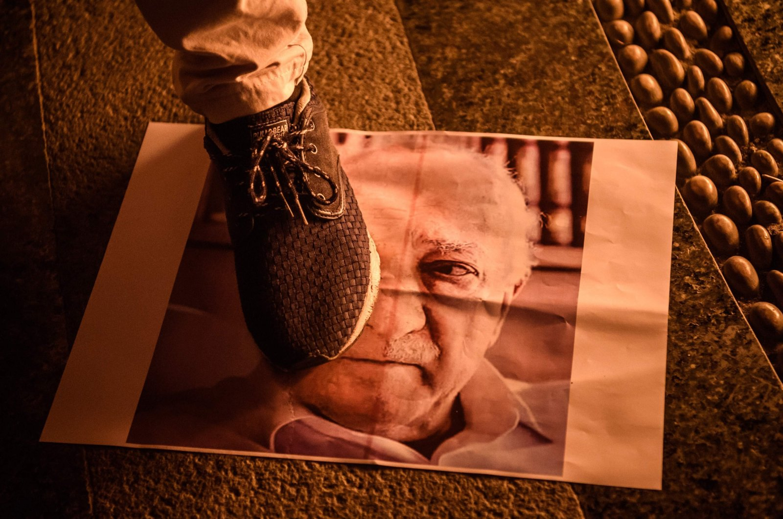 A protester walks on a poster of FETÖ leader Fetullah Gülen in a rally to condemn FETÖ's coup attempt, in Istanbul, Turkey, July 18, 2016. (AFP PHOTO)