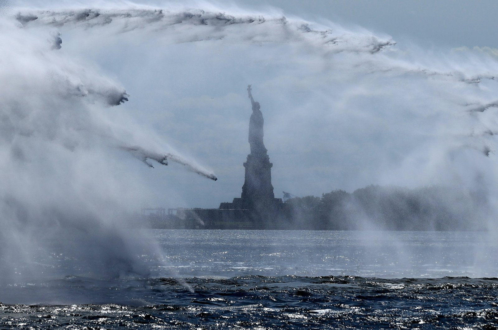 The Statue of Liberty is seen through the spray created during the 20th-anniversary commemoration of 9/11 along Lower Manhattan, New York City., U.S., Sept. 10, 2021. (Photo by Getty Images)