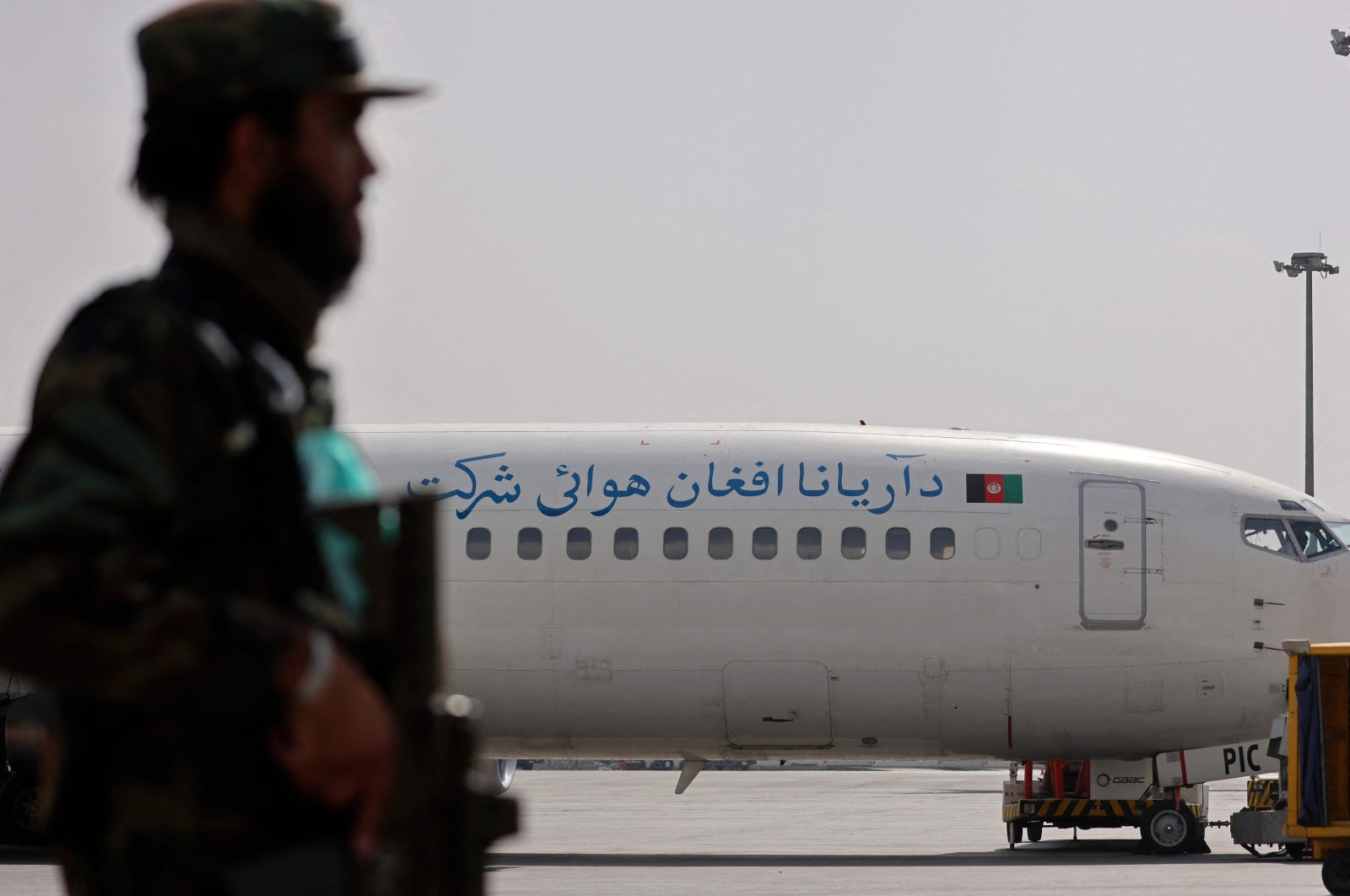 A Taliban fighter stands guard next to an Ariana Afghan Airlines aircraft on the tarmac at the airport in Kabul, Afghanistan, Sept. 12, 2021. (AFP Photo)