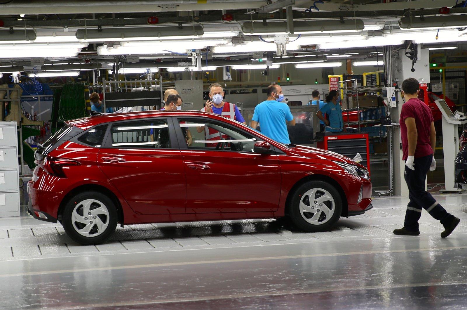 Workers are seen beside a car at Hyundai Assan's Izmit factory in northwestern Kocaeli, Turkey, Aug. 28, 2020. (AA Photo)