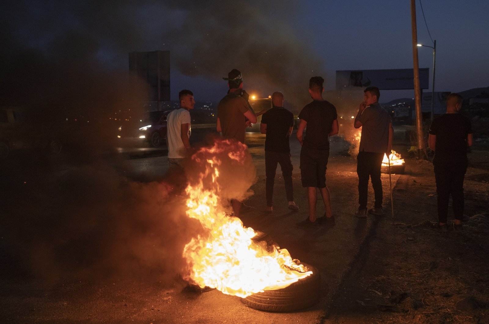 Protesters set tires on fire during clashes with Israeli troops following a demonstration supporting Palestinian prisoners in Israeli jails, at the entrance of the West Bank city of Nablus, Palestine, Monday, Sept. 13, 2021. (AP Photo)