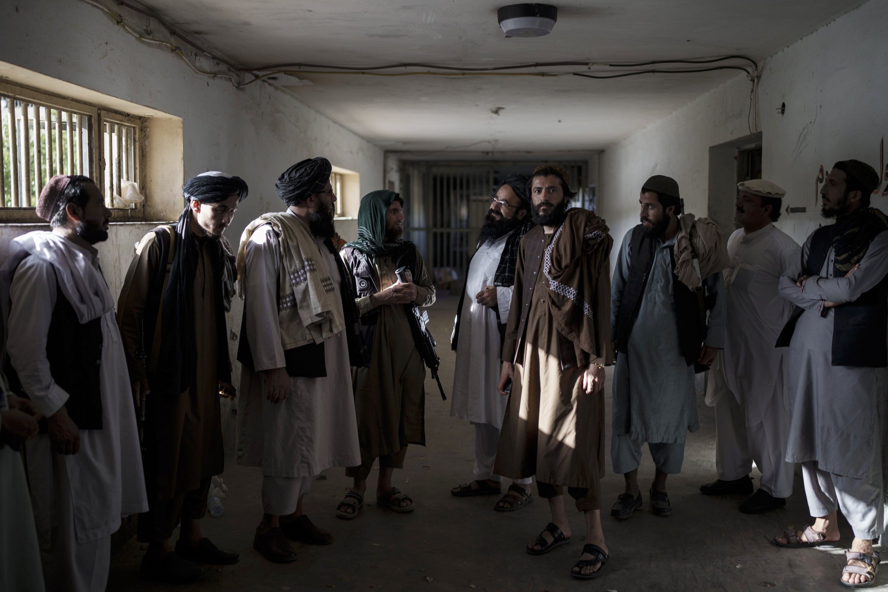 Taliban fighters, some former prisoners, chat in an empty area of the Pul-e-Charkhi prison in Kabul, Afghanistan, Sept. 13, 2021. (AP Photo)