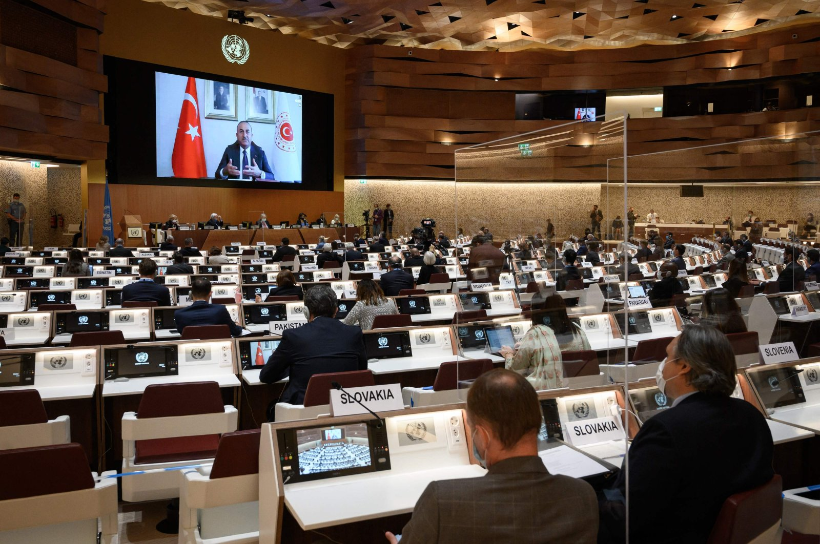 Delegates watch a remote speech by Turkish Foreign Minister Mevlüt Çavuşoğlu on a giant screen during an aid conference on Afghanistan, in Geneva, Switzerland, Sept. 13, 2021. (AFP Photo)
