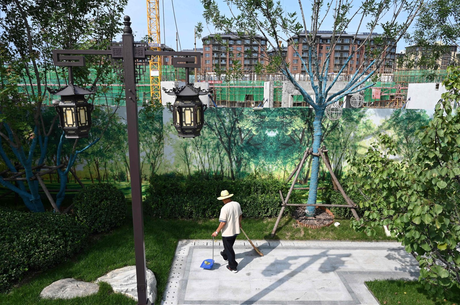 A worker cleans a display area next to the construction site of an Evergrande housing complex in Beijing, China, Sept. 13, 2021. (AFP Photo)