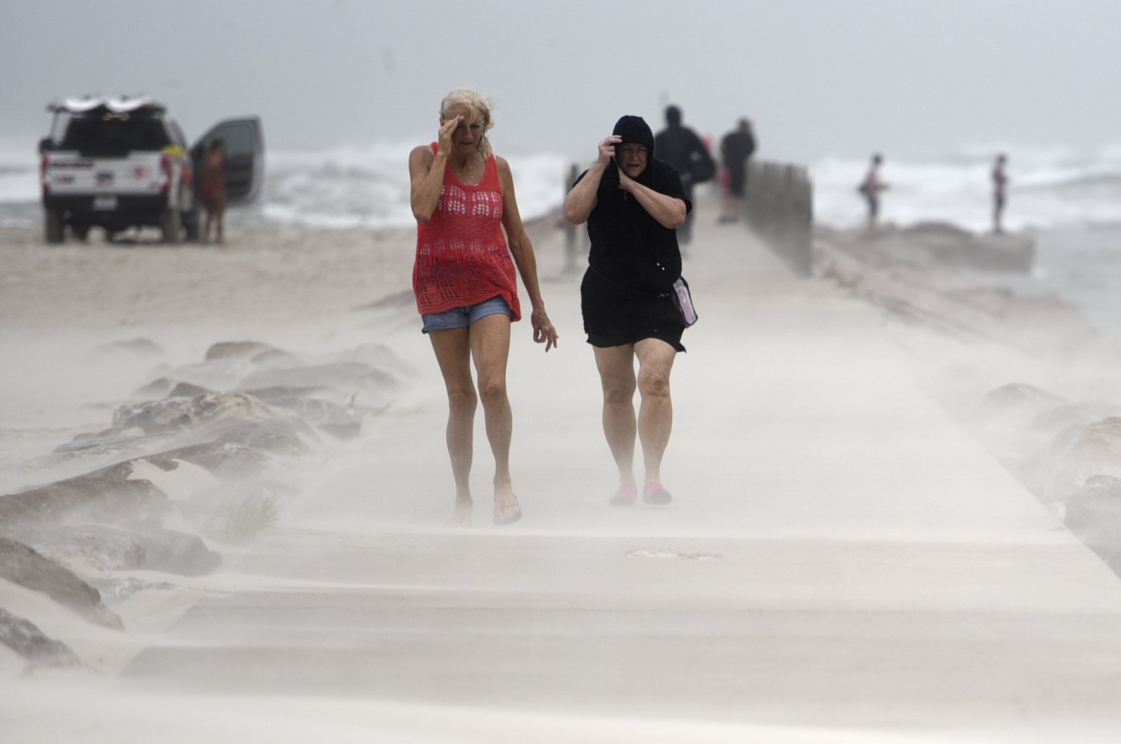 People shield their faces from wind and sand ahead of Tropical Storm Nicholas on the North Packery Channel jetty in Corpus Christi, Texas, U.S, Monday, Sept. 13, 2021. (AP Photo)