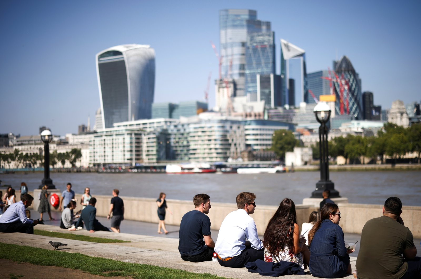 The City of London financial district can be seen in the background as people relax in the sunny weather on the south side of the River Thames in London, Britain, Sept. 7, 2021. (Reuters Photo)