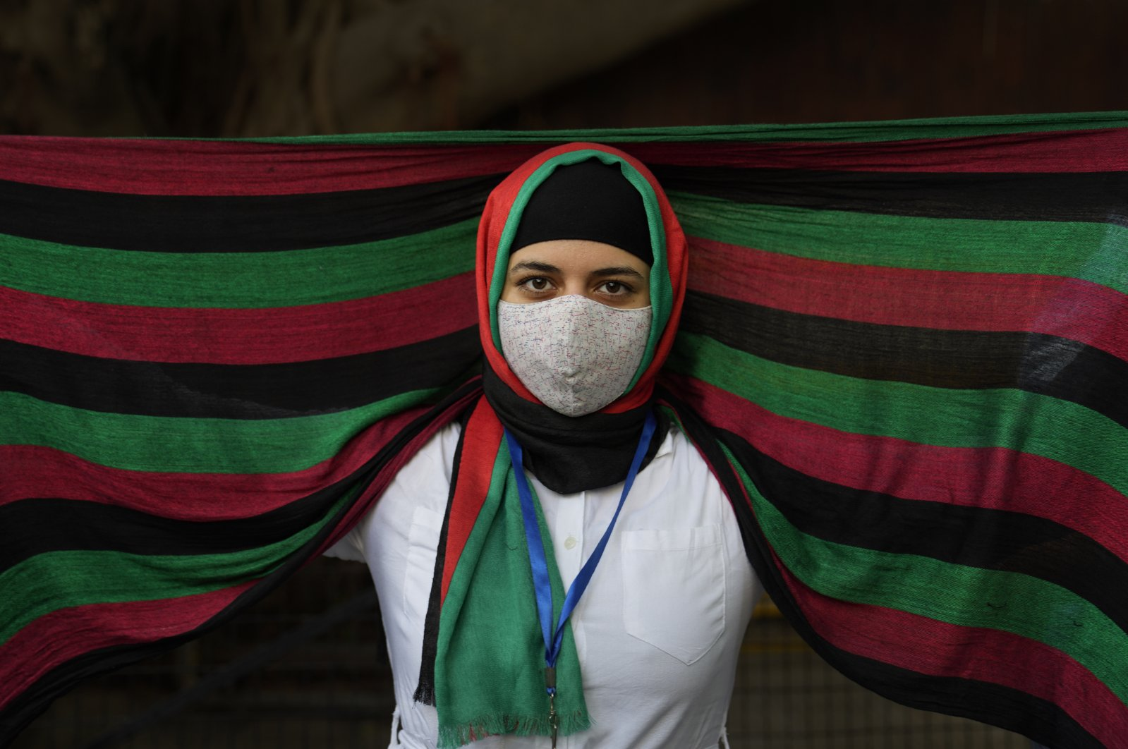 An Afghan refugee living in India wearing a scarf in the colors of the Afghan flag participates in a protest against the Taliban takeover of Afghanistan outside the office of the United Nations High Commissioner for Refugees, in New Delhi, India,  Aug. 23, 2021. (AP Photo)