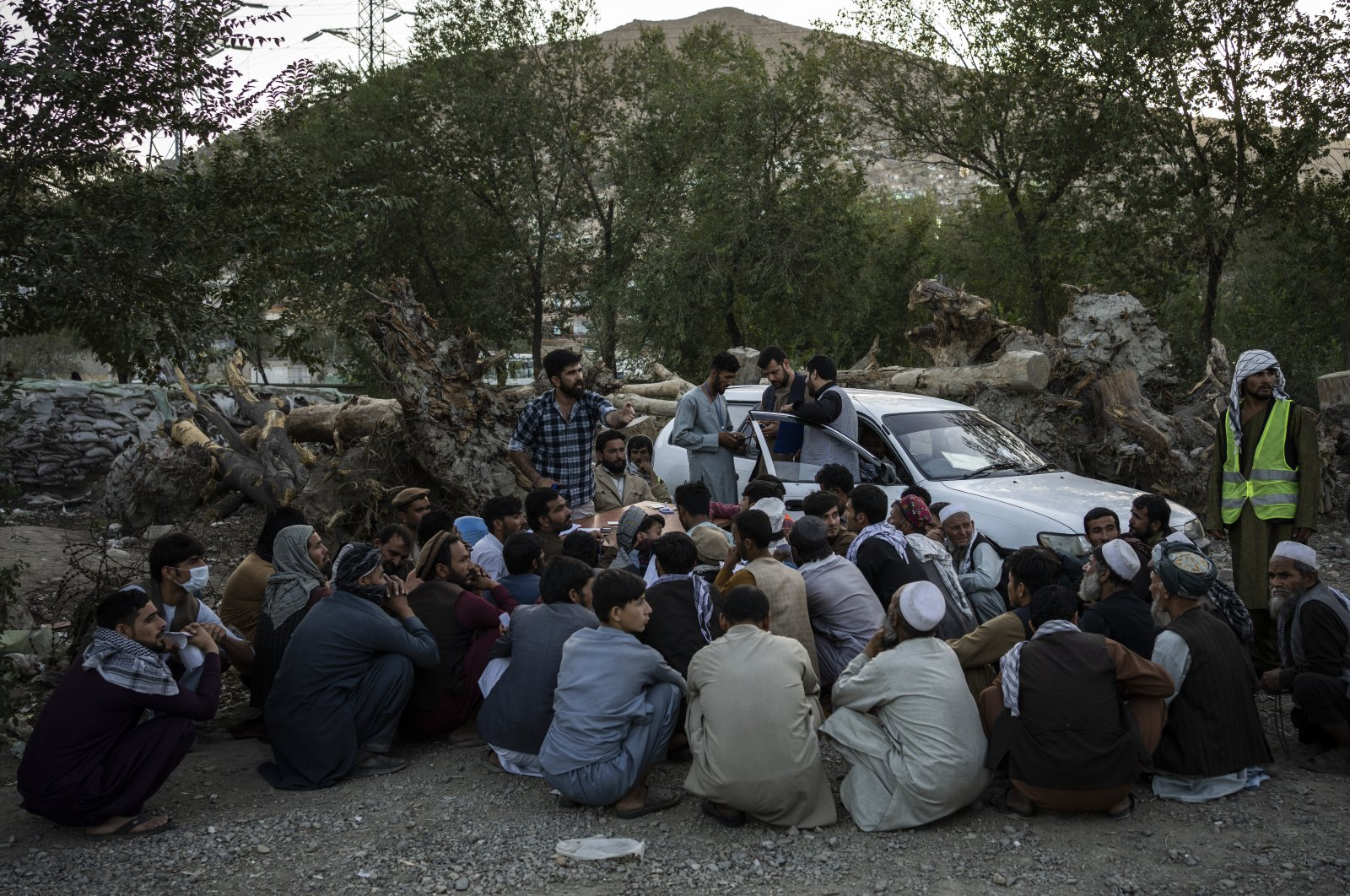 Displaced Afghans wait for food donations at a camp for internally displaced persons in Kabul, Afghanistan, Sept. 13, 2021. (AP Photo)