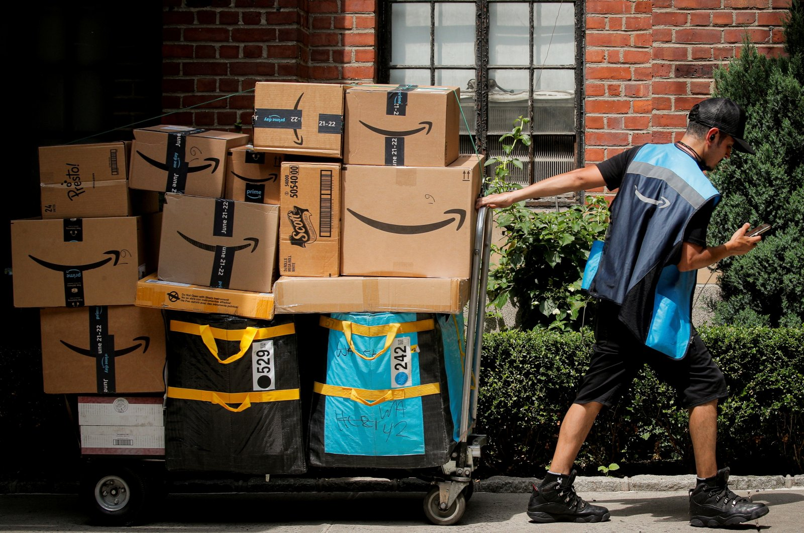 An Amazon delivery worker pulls a delivery cart full of packages during its annual Prime Day promotion in New York City, U.S., June 21, 2021. (Reuters Photo)