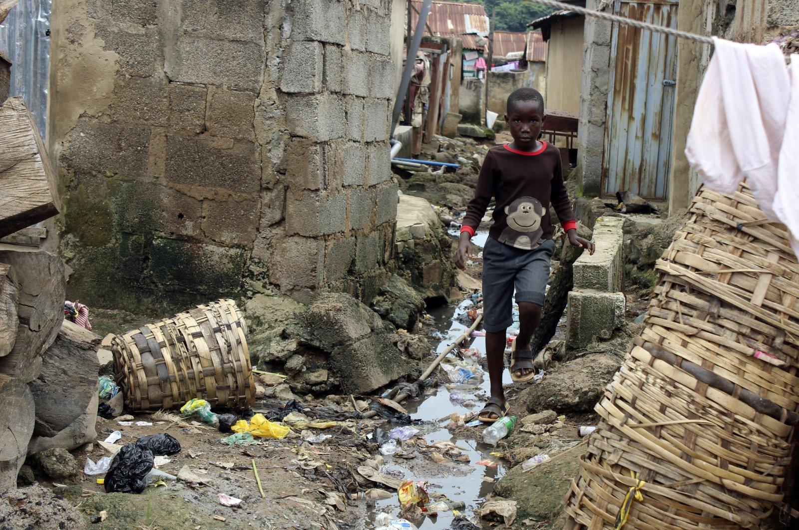 A boy walks past sewage around houses in Abuja, Nigeria, Sept. 3, 2021. (AP Photo)
