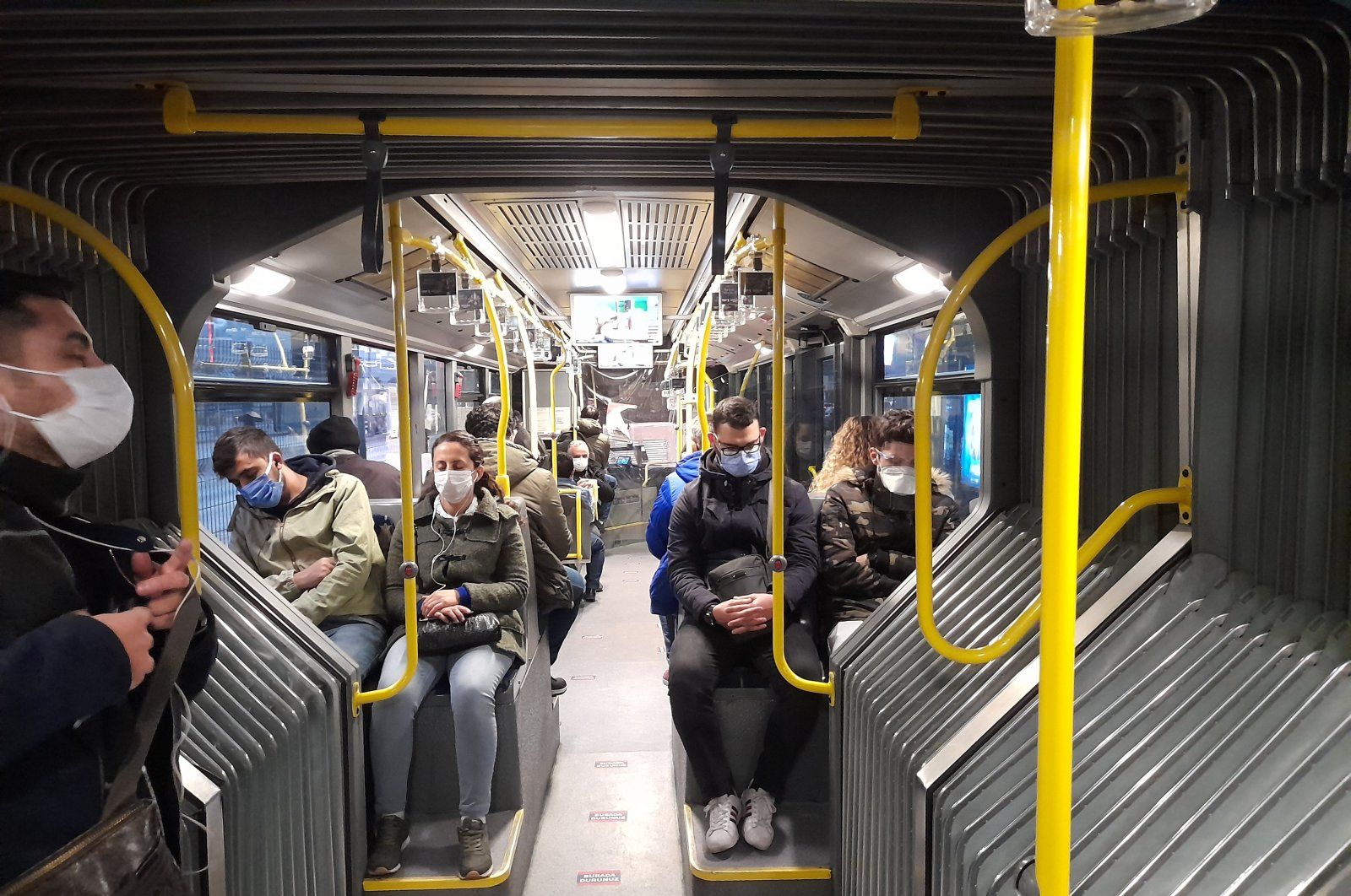 People travel in a largely empty metrobus, in Istanbul, Turkey, Dec. 11, 2020. (PHOTO BY ALİ OKTAY)