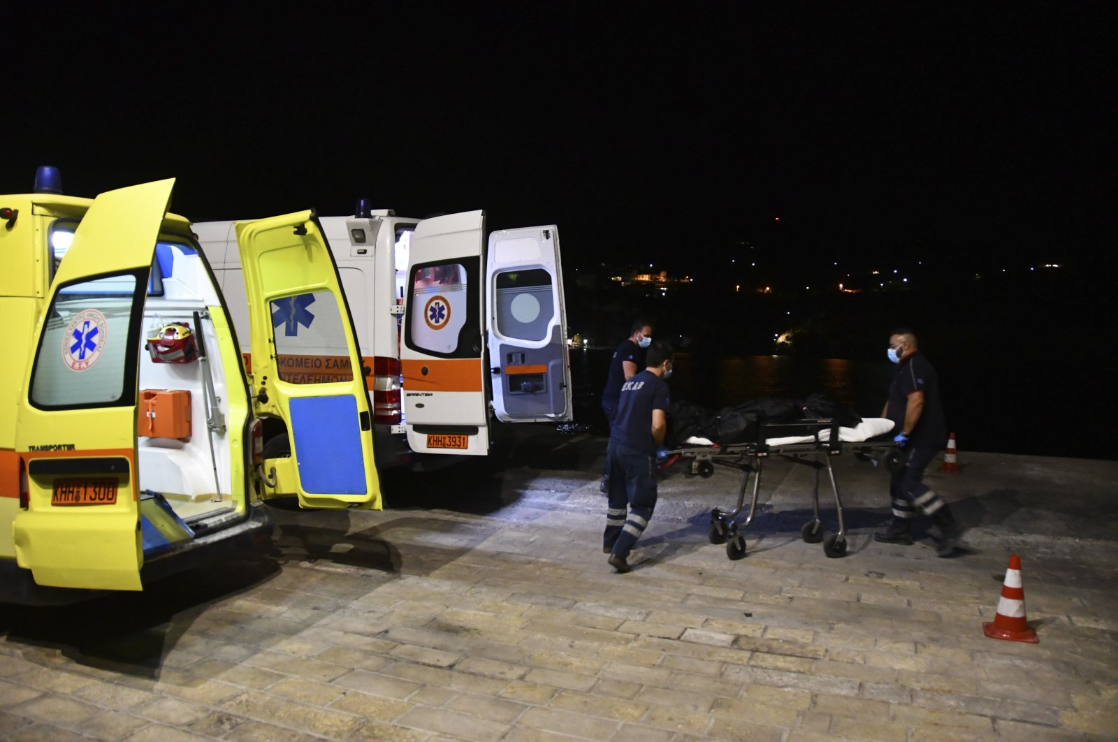 Paramedics wheel a gurney with a body at Pythagorio port, on the eastern Aegean island of Samos, Greece, Sept. 13, 2021. (AP Photo)