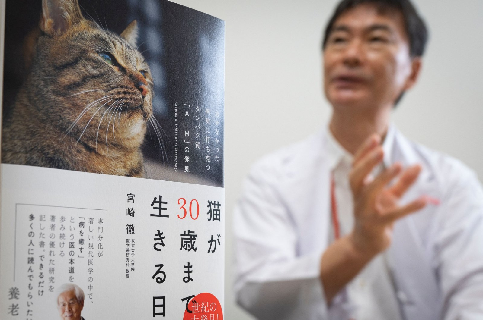 Immunology professor Toru Miyazaki explaining his study behind a copy of his book (L) during an interview with AFPBB News at the University of Tokyo, Tokyo, Japan, July 30, 2021. (AFPBB News via AFP)