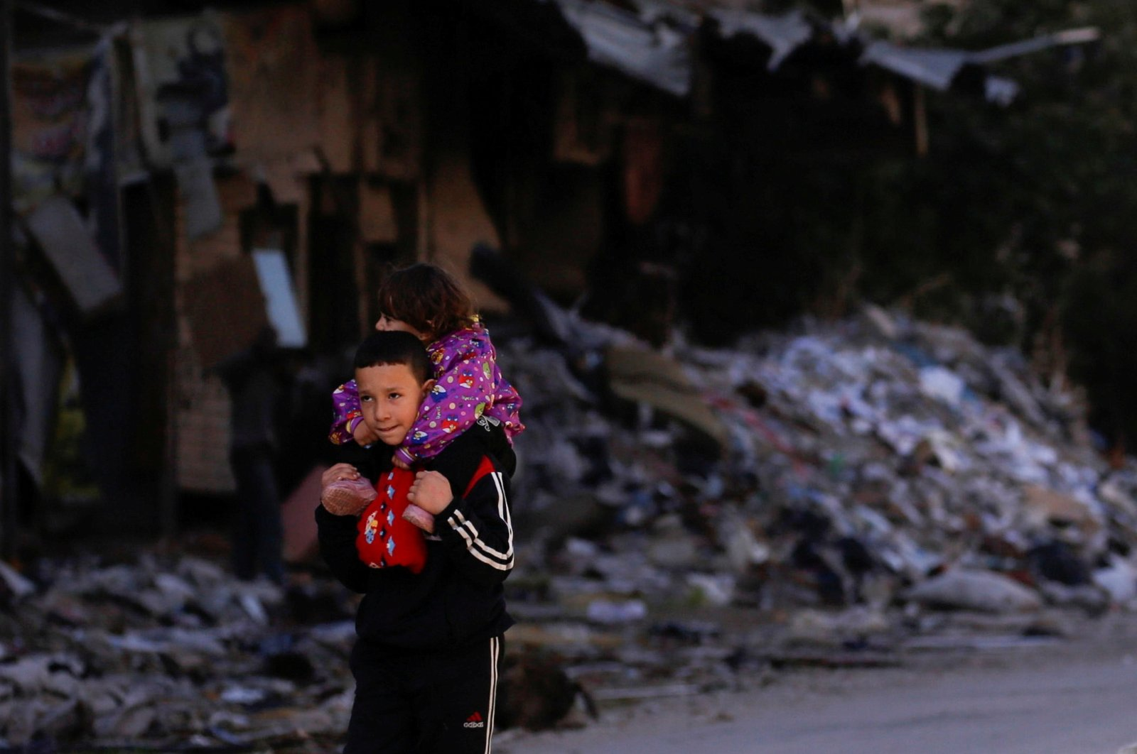A boy carries a child past damaged buildings at the Yarmouk Palestinian refugee camp on the southern outskirts of Damascus, Syria, Dec. 1, 2020. (Reuters Photo)