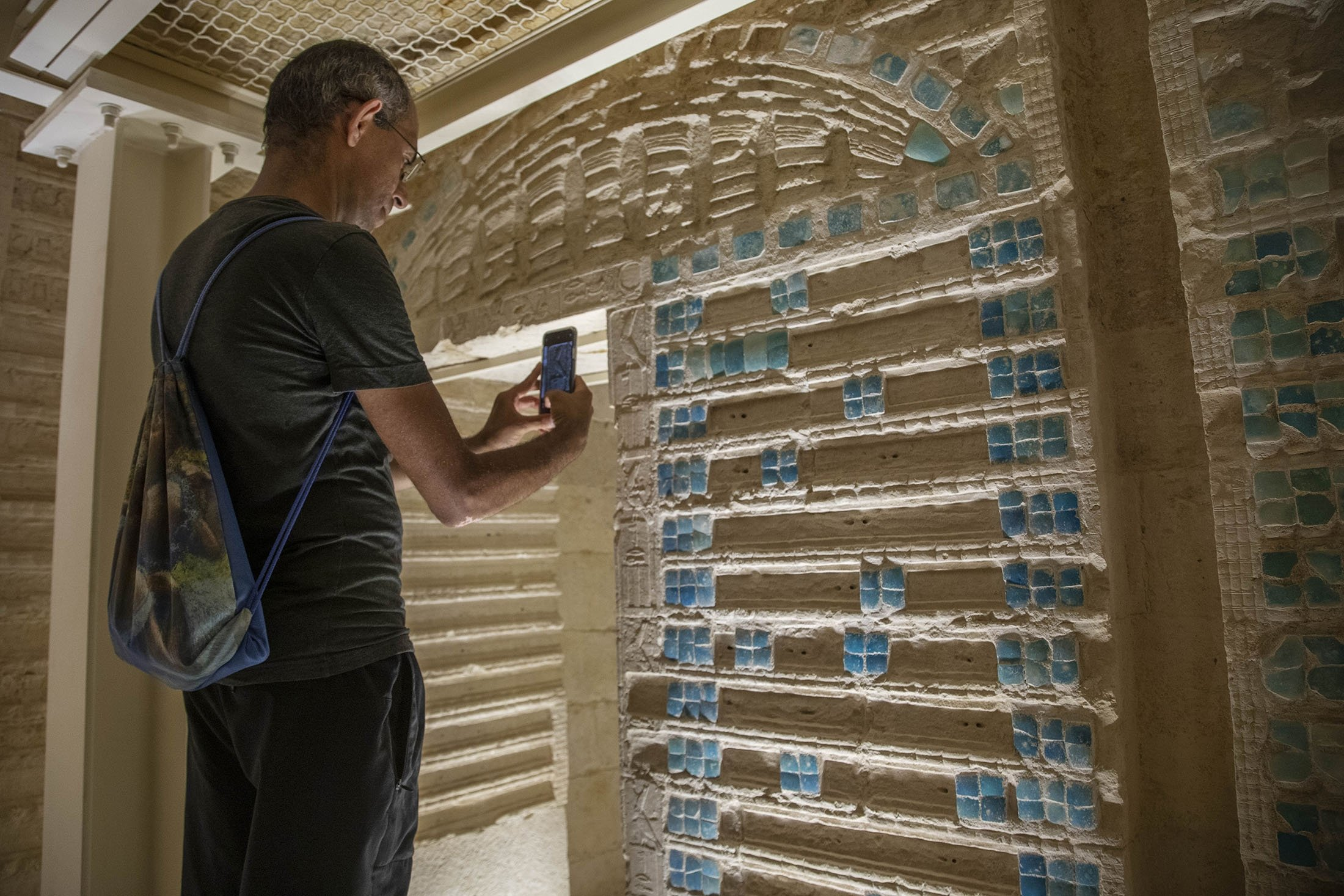 An archaeologist takes photos of inscriptions on the wall of the southern cemetery of King Djoser, after its restoration, near the famed Step Pyramid, in Saqqara, south of Cairo, Egypt, Sept. 14, 2021. (AP Photo)