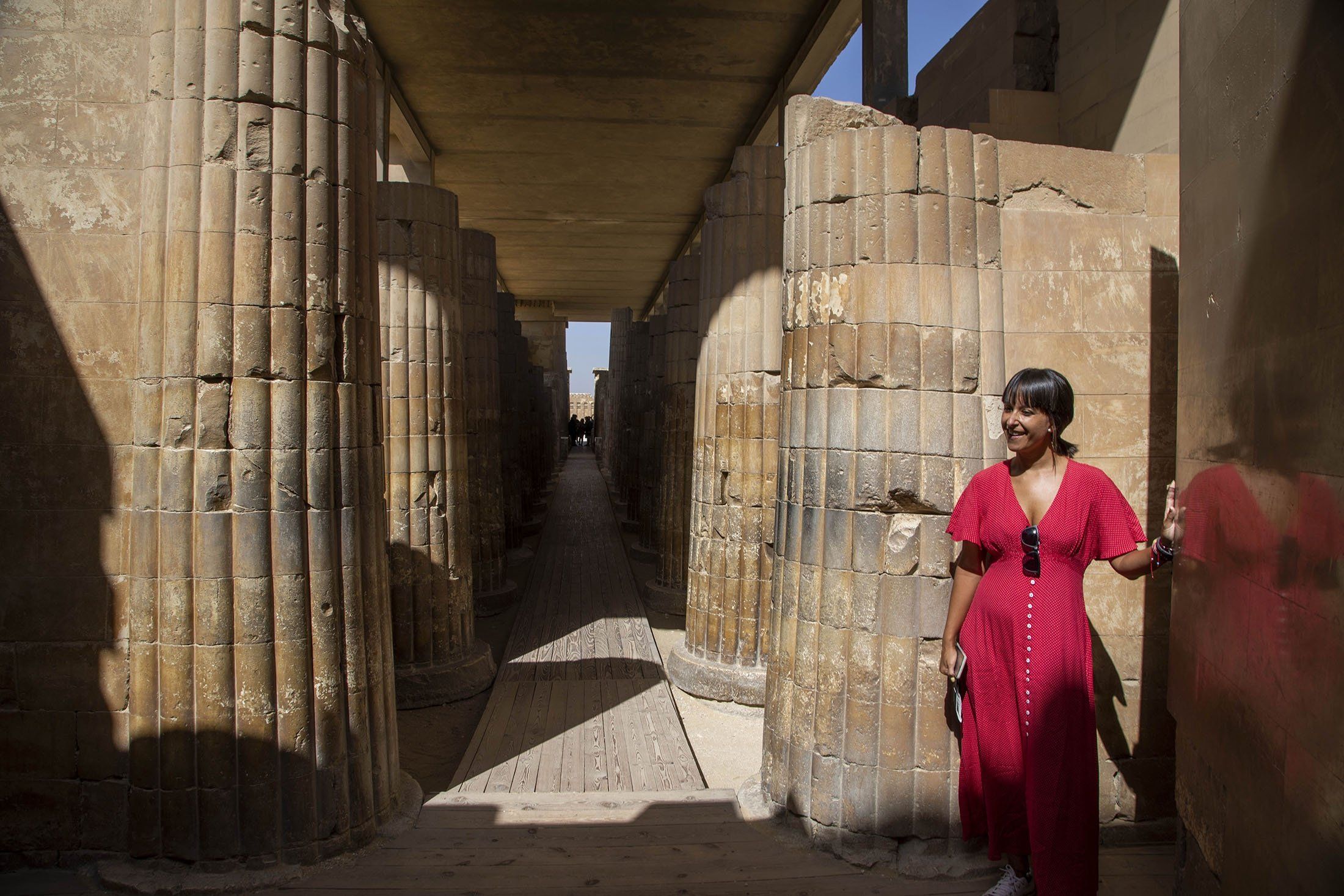 A tourist listens to a guide speak at the entrance of the southern cemetery of King Djoser, after its restoration, near the famed Step Pyramid, in Saqqara, south of Cairo, Egypt, Sept. 14, 2021. (AP Photo)