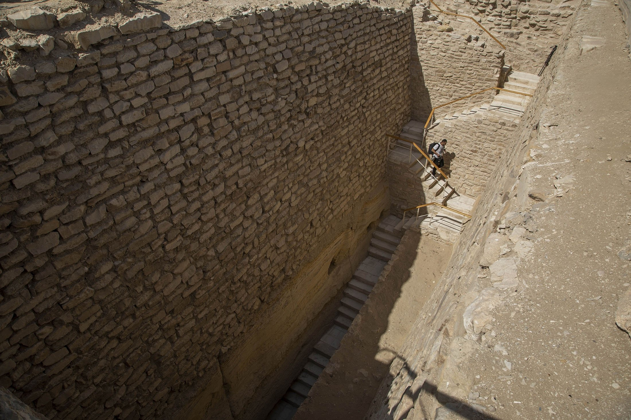 A journalist walks down stairs towards the southern cemetery of King Djoser, after its restoration, near the famed Step Pyramid, in Saqqara, south of Cairo, Egypt, Sept. 14, 2021. (AP Photo)