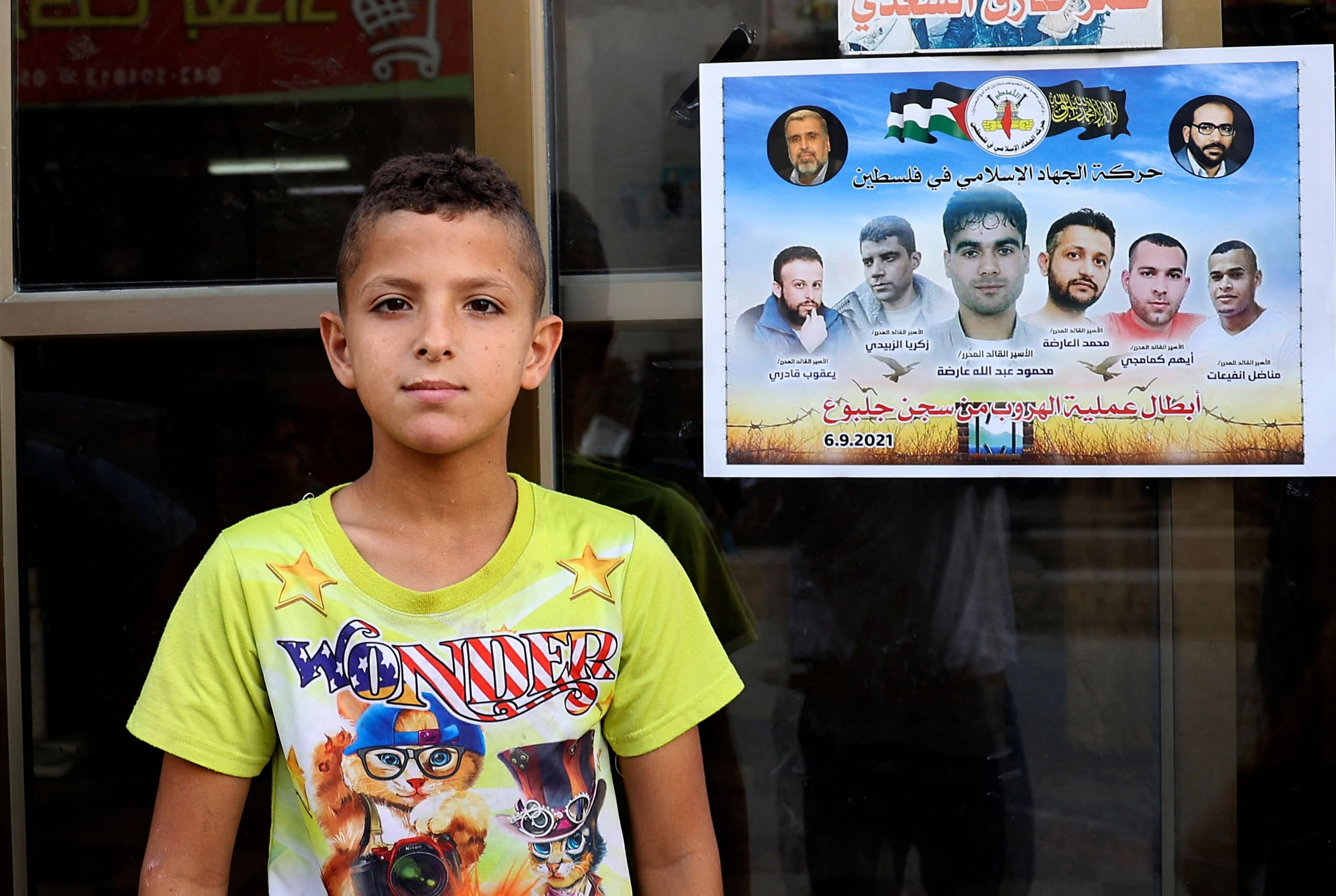 A Palestinian child looks on while standing next to a poster expressing solidarity with the six Palestinian prisoners who escaped from Israel's Gilboa prison, hanging outside a shop at the Jenin camp for Palestinian refugees in the north of the occupied West Bank, Palestine, Sept. 12, 2021. (Photo by JAAFAR ASHTIYEH via AFP)