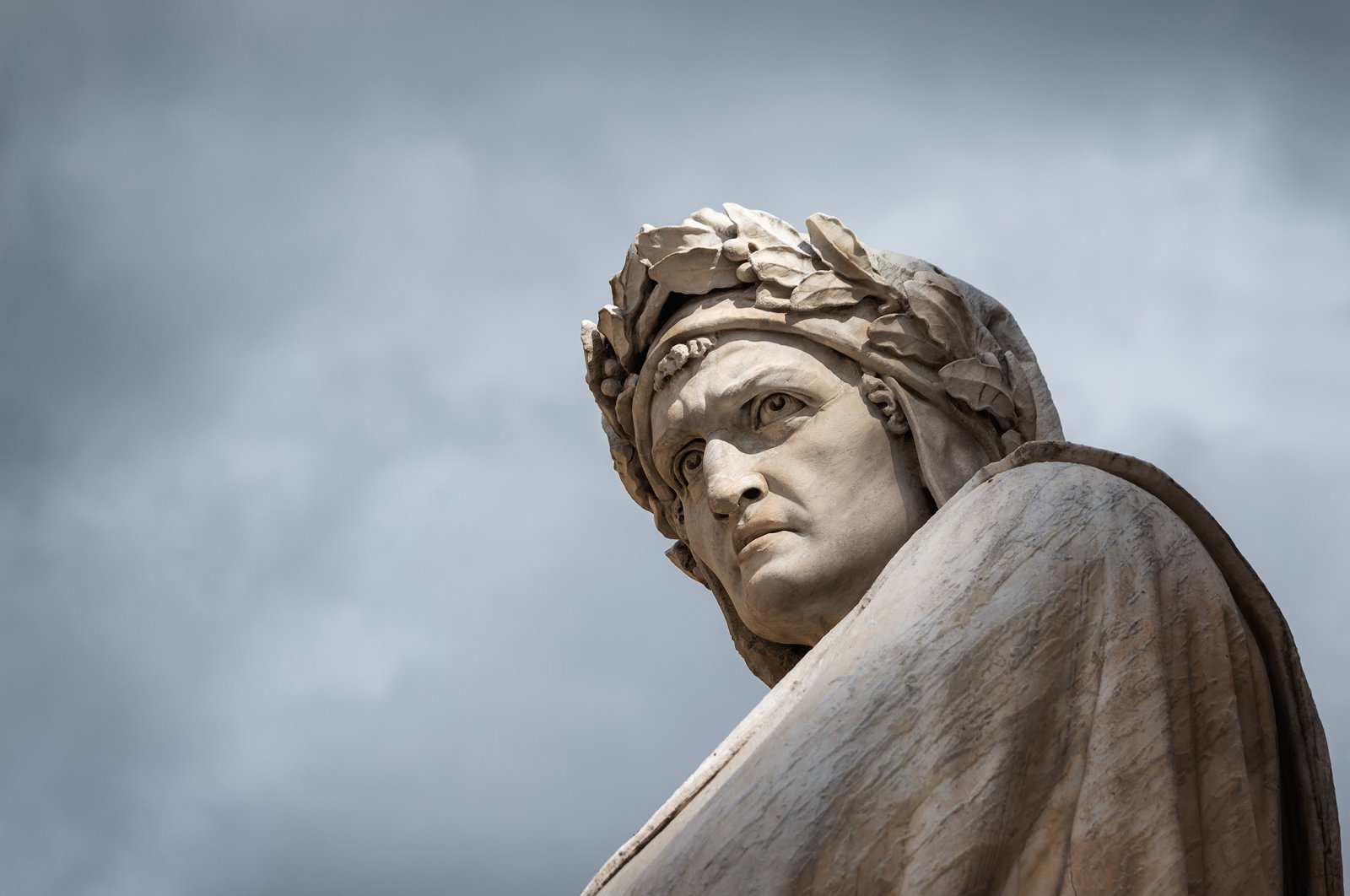 Close-up shot of the famous white marble monument of Dante Alighieri by  Enrico Pazzi in Piazza Santa Croce, next to Basilica of Santa Croce, Florence, Italy. (Shutterstock Photo)