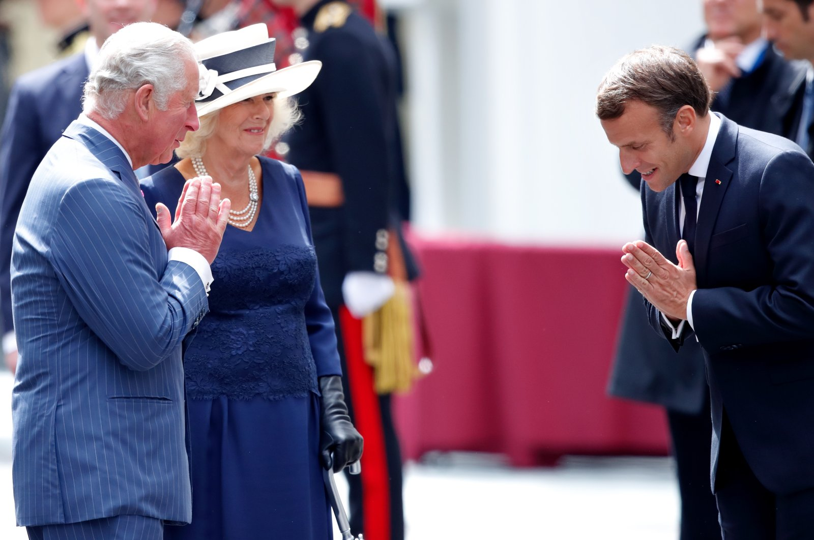 Prince Charles, Prince of Wales, accompanied by Camilla, Duchess of Cornwall, and French President Emmanuel Macron make namaste hand gestures as they say goodbye after attending a ceremony in Carlton Gardens, London, U.K., June 18, 2020. (Photo by Getty Images)