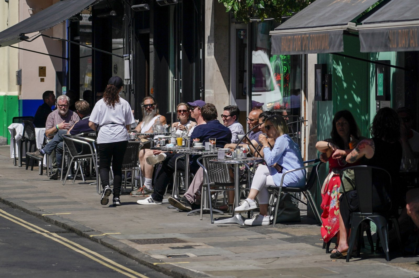 People sit at outdoor tables at a restaurant in Soho, in London, June 14, 2021. (AP Photo)
