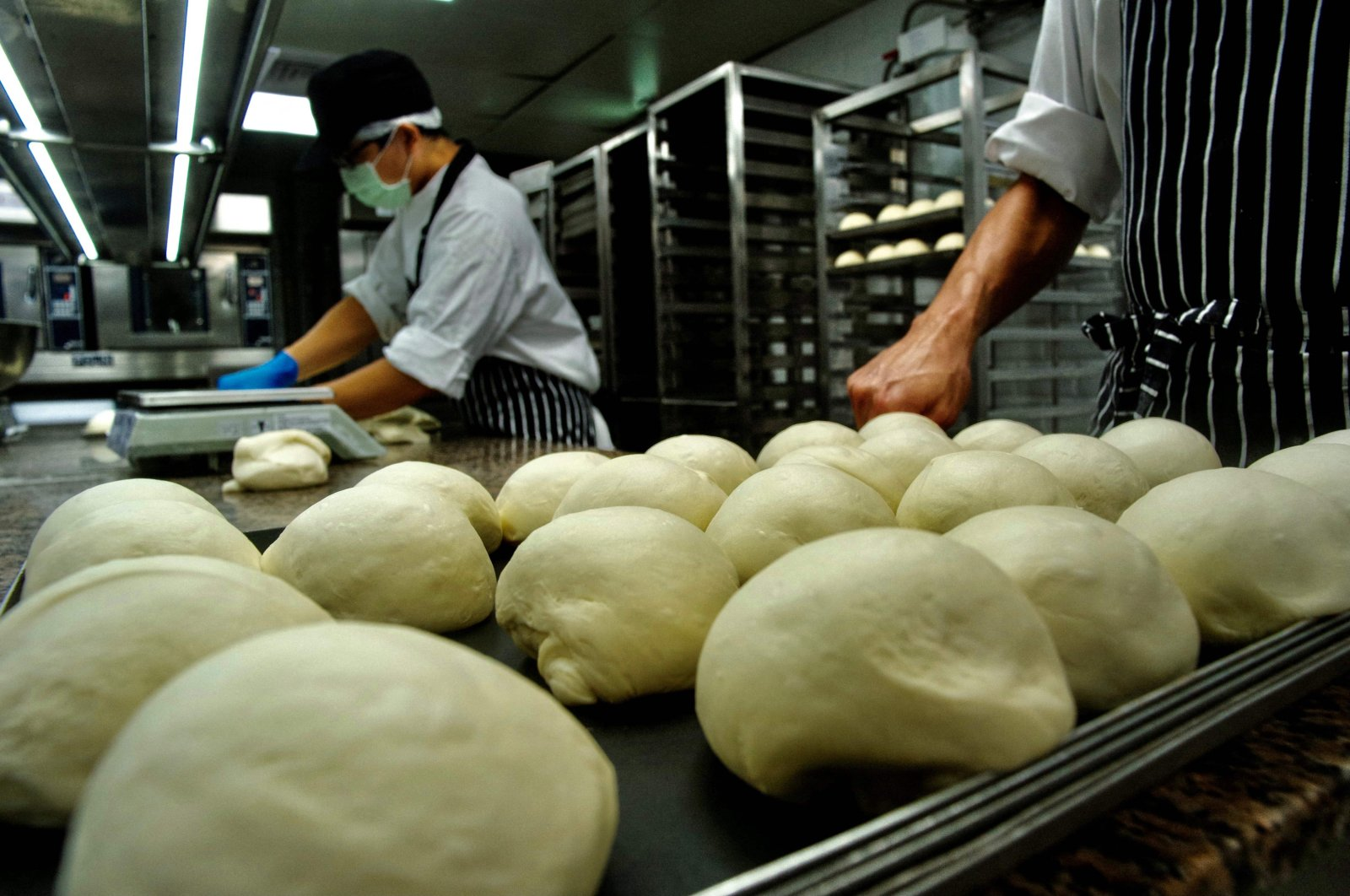 """Employees from Taiwan company Just Kitchen, a network of """"ghost kitchens"""" that make delivery-only food, preparing to bake bread for takeaway meals at one of their locations in Taipei, Taiwan, Aug. 18, 2021. (Sam Yeh / AFP Photo)"""