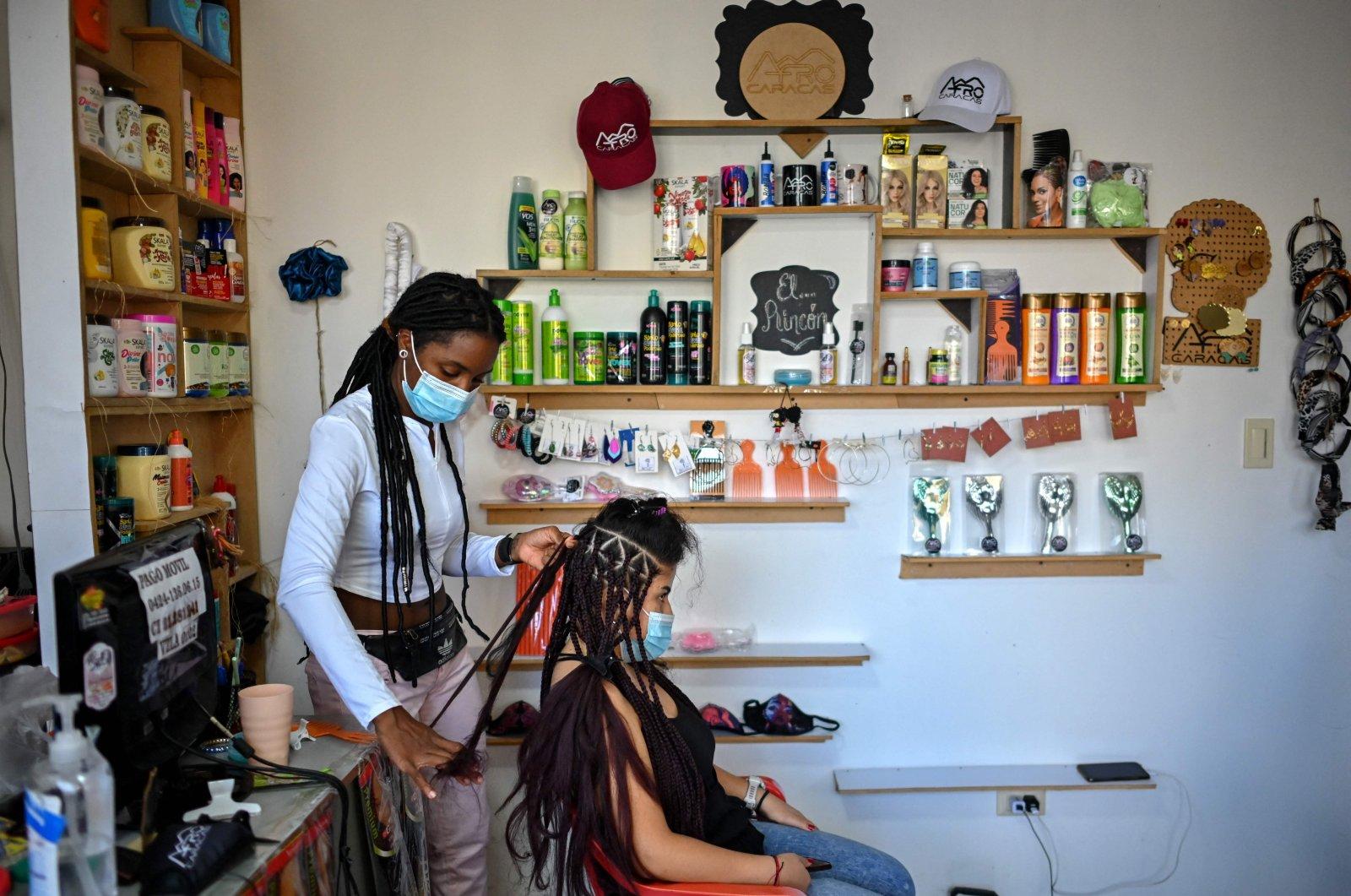 A hairdresser braids a customer's hair at a beauty salon, in downtown Caracas, Venezuela, Sept. 1, 2021. (AFP Photo)
