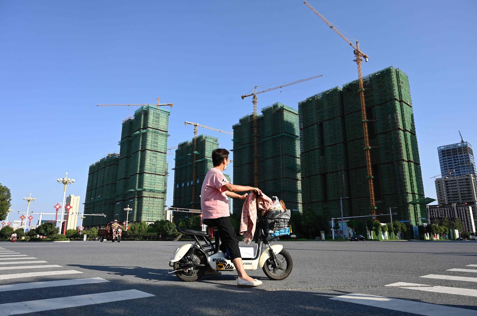 A woman rides a scooter past the construction site of an Evergrande housing complex in Zhumadian, Henan province, central China, Sept. 14, 2021. (AFP Photo)