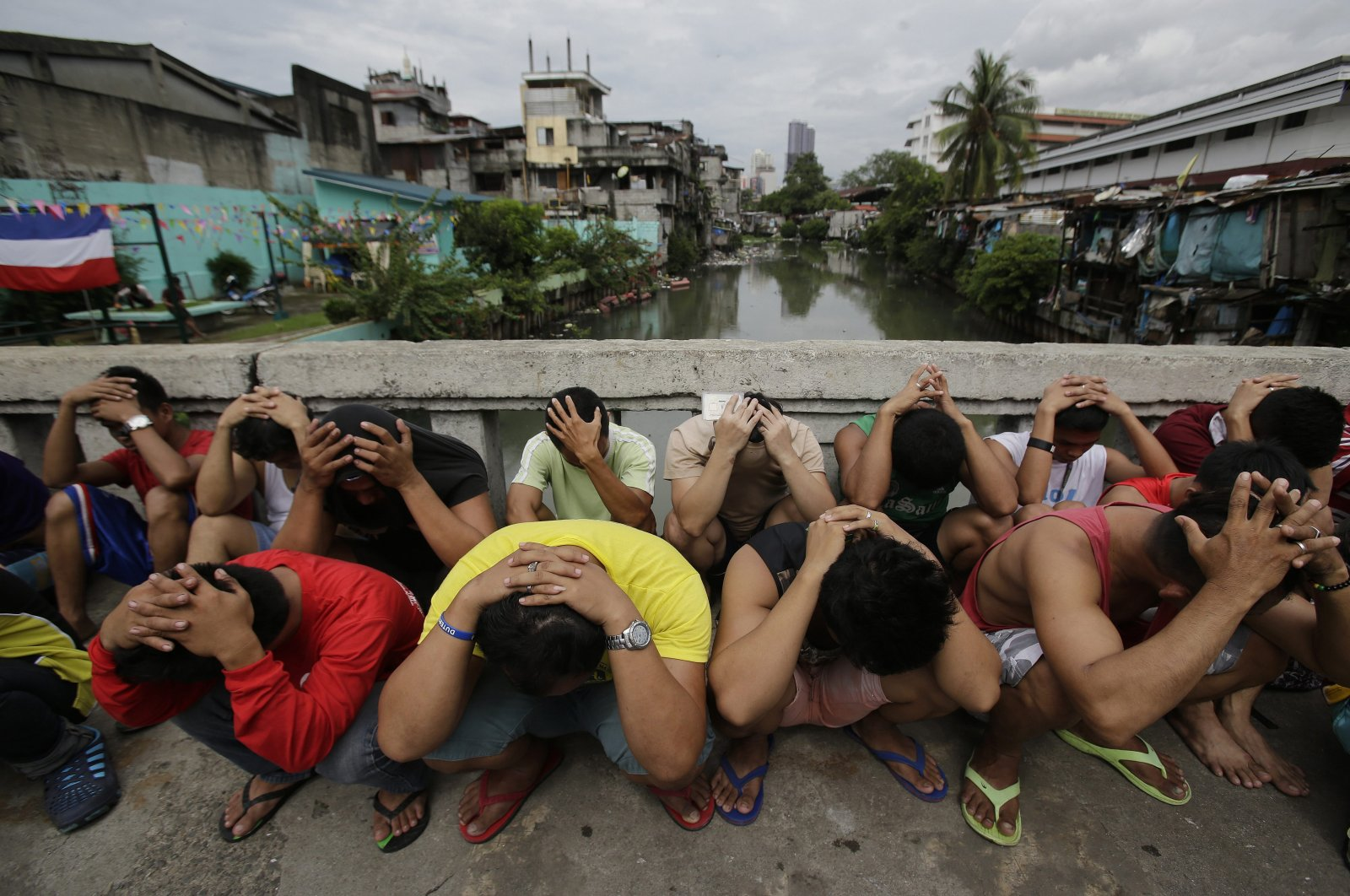 """Filipino men place their hands over their heads as they are rounded up during a police operation as part of the continuing """"War on Drugs"""" campaign of Philippine President Rodrigo Duterte in Manila, Philippines, Oct. 7, 2016. (AP Photo)"""