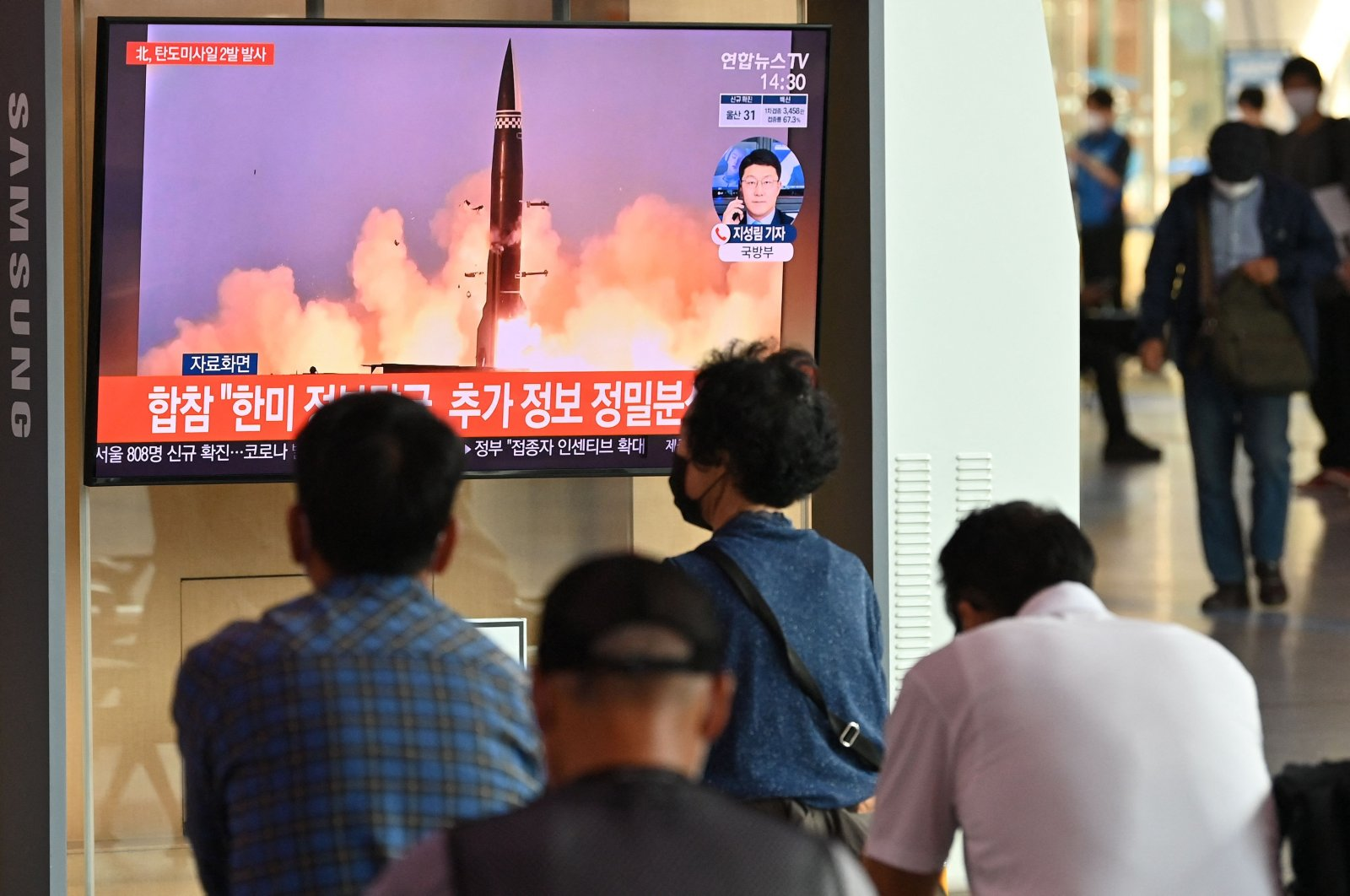 People watch a television news broadcast showing file footage of a North Korean missile test, at a railway station in Seoul on Sept. 15, 2021, after North Korea fired two ballistic missiles into the sea, according to the South's military. (AFP Photo)