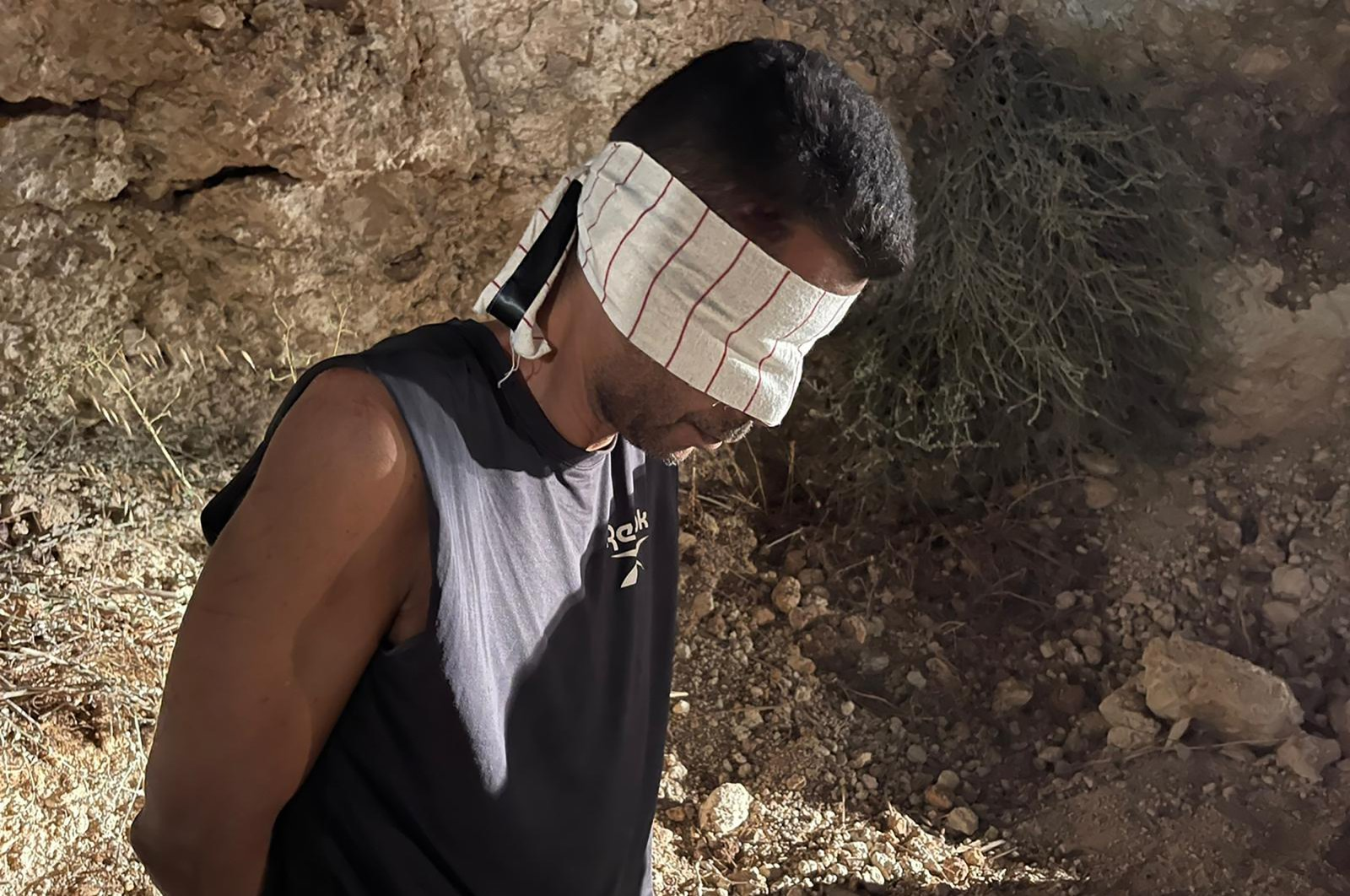 Zakaria Zubeidi, one of the six Palestinians who escaped from a high-security prison earlier this week, is blindfolded and handcuffed after being recaptured in the town of Umm al-Ghanam, northern Israel, Sept. 11, 2021. (Israeli Police via AP, File)
