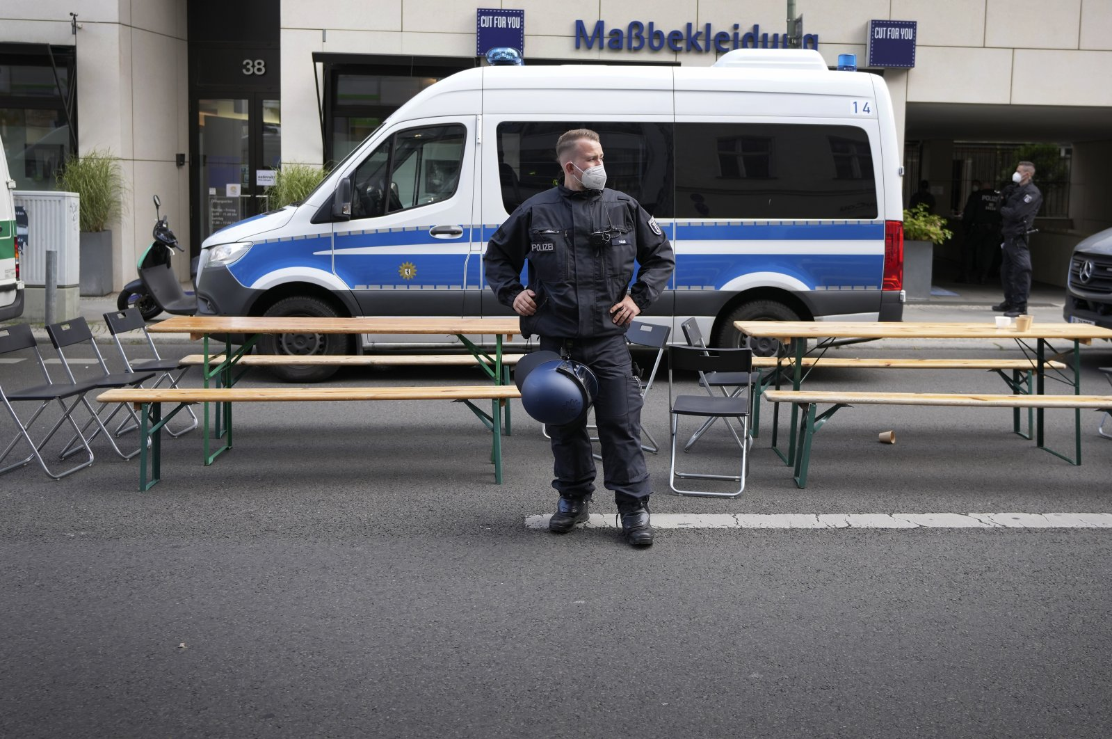 A member of the police forces stands in front of benches, chairs and tables, set up by the police, in a road next to a protest rally of the 'Extinction Rebellion' movement in front of the 'House Of The Economic Council' (the business association of the German Christian Democratic Union, CDU) in Berlin, Germany, Wednesday, Aug. 18, 2021. (AP File Photo)