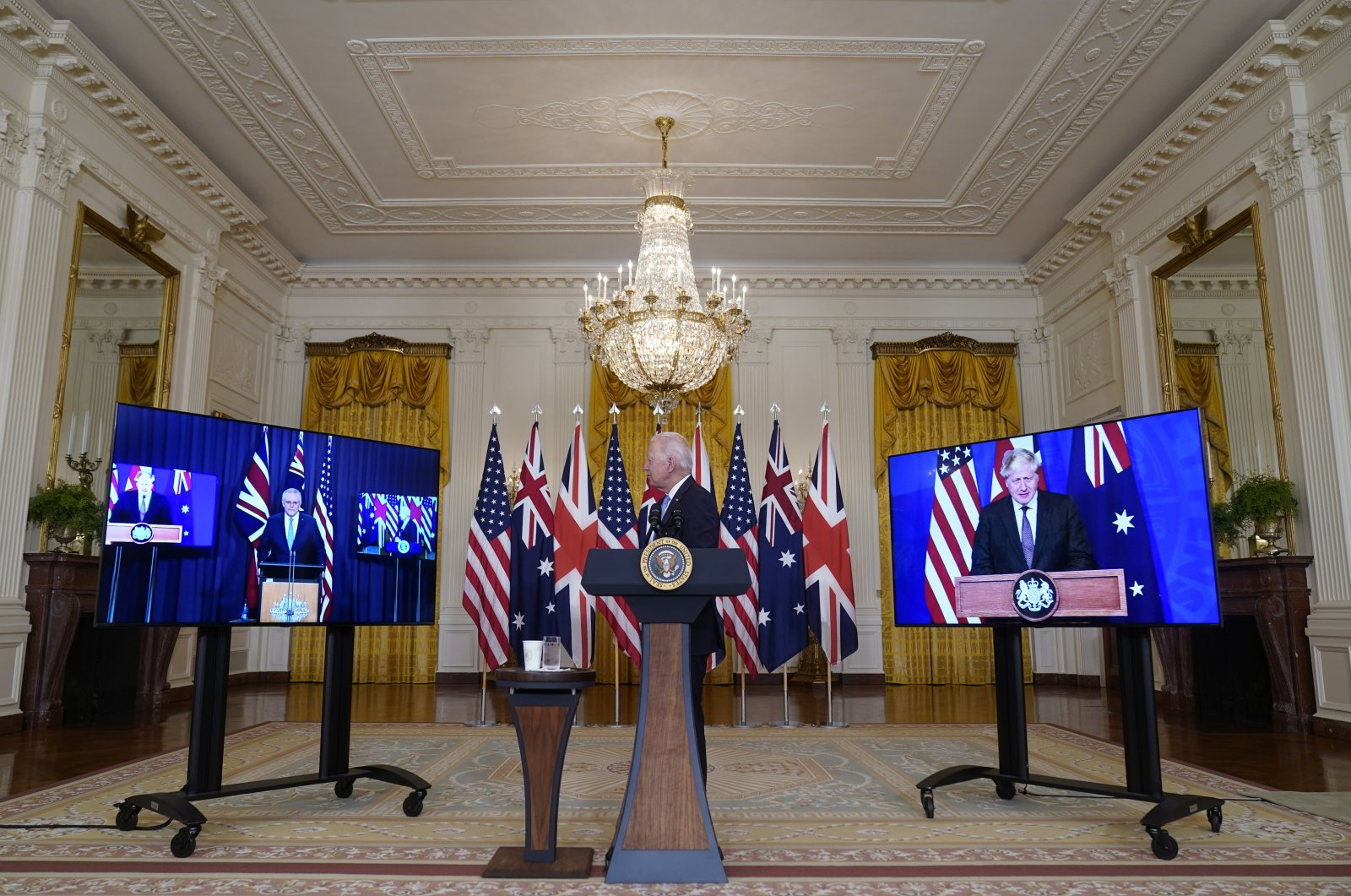U.S. President Joe Biden, listens as he is joined virtually by Australian Prime Minister Scott Morrison, left, and British Prime Minister Boris Johnson, speaks about a national security initiative in the East Room of the White House in Washington, Wednesday, Sept. 15, 2021. (AP Photo)