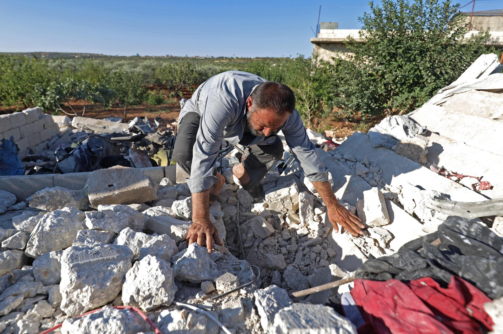 A man searches through rubble in the aftermath of Syrian regime forces' bombardment on the town of Balashun, south of Idlib province, Syria, on Aug. 19, 2021. (AFP Photo)