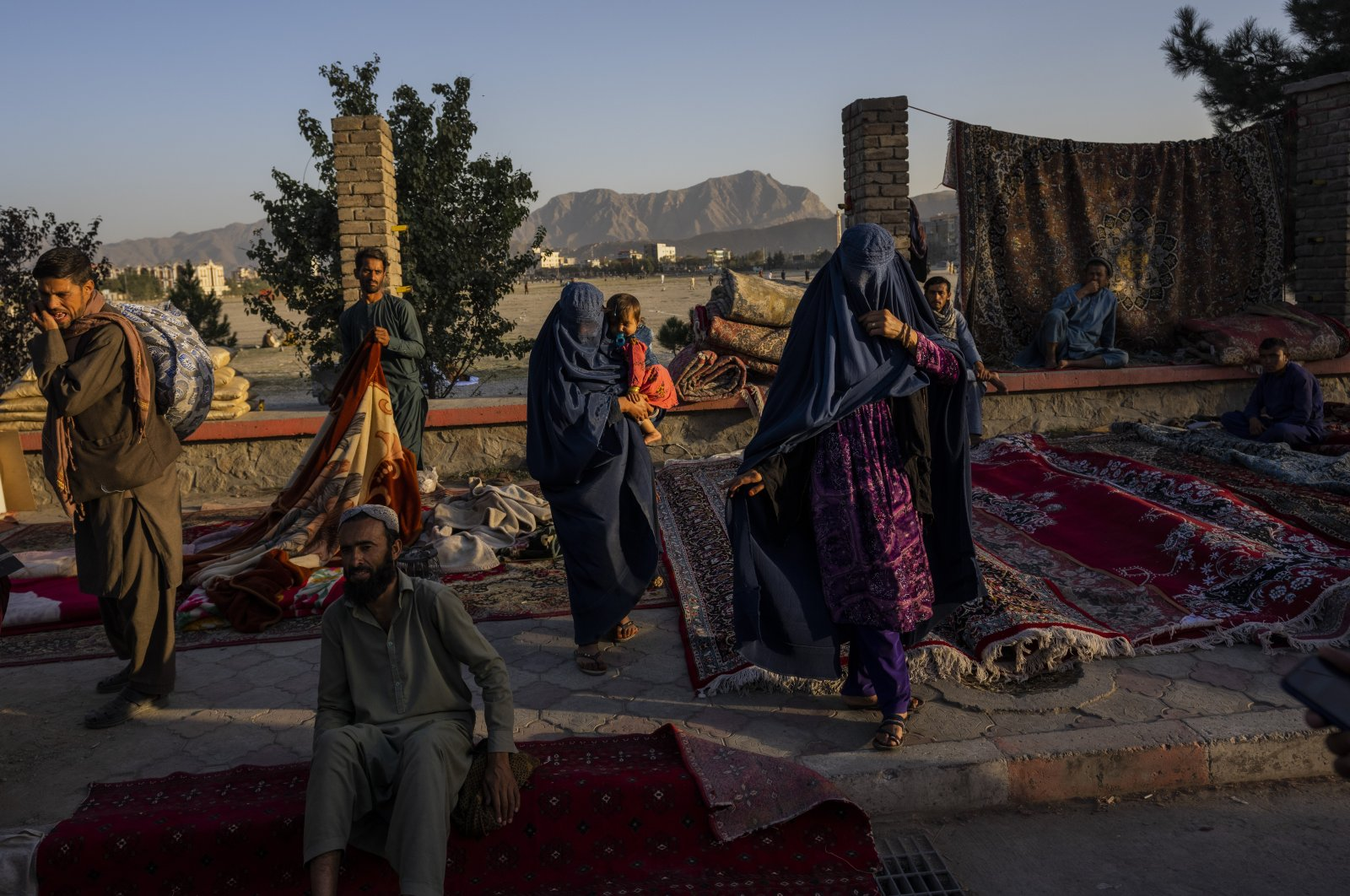 Afghan women walk through a second-hand market where many families sold their belongings before leaving the country or due to financial struggle, in Kabul, Afghanistan, Sept. 15, 2021. (AP Photo)