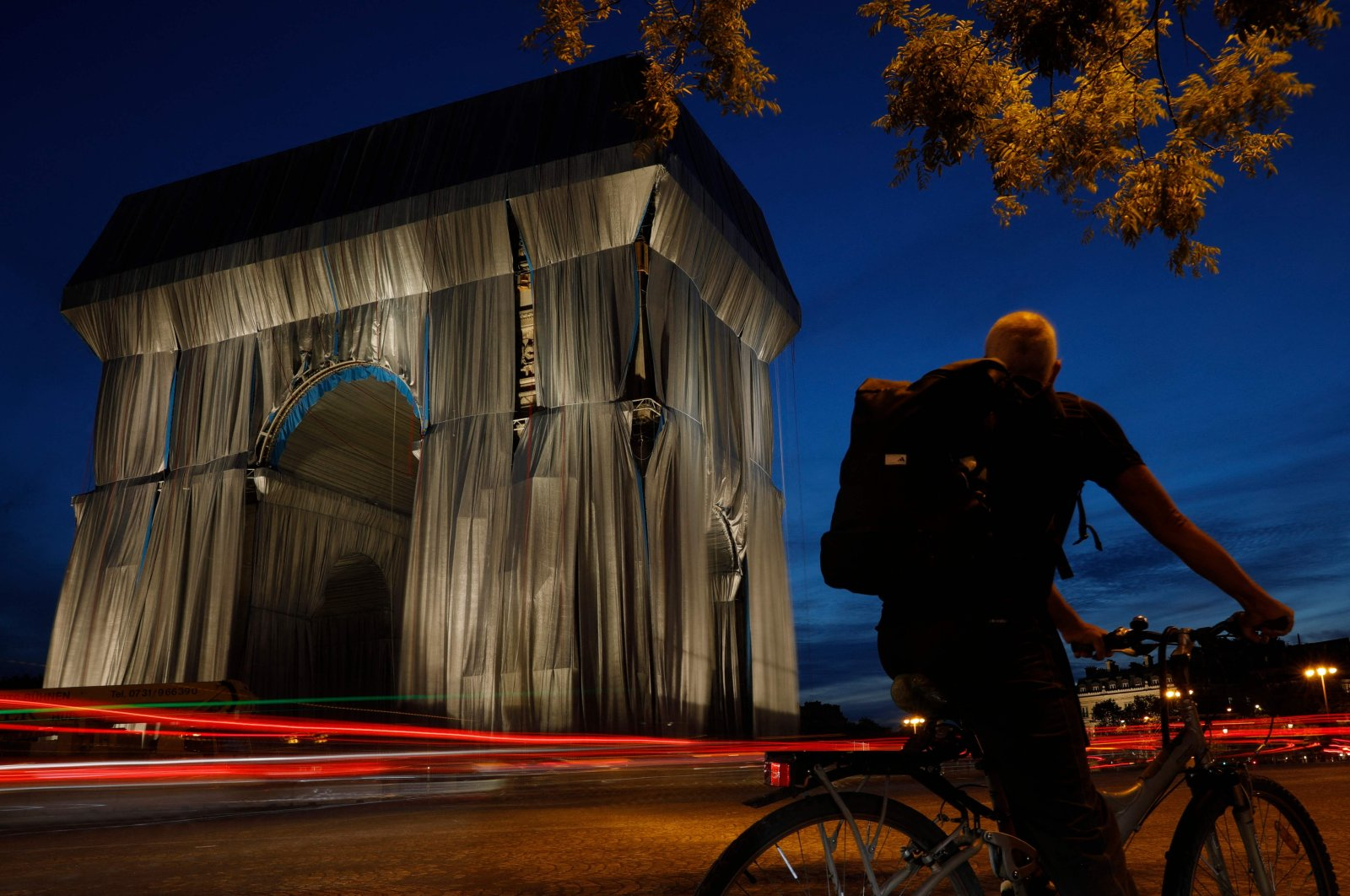 A cyclist looks at the Arc de Triomphe, in Paris, wrapped in silver-blue fabric as it was designed by the late artist Christo, Paris, France, Sept. 13, 2021. (AFP Photo)