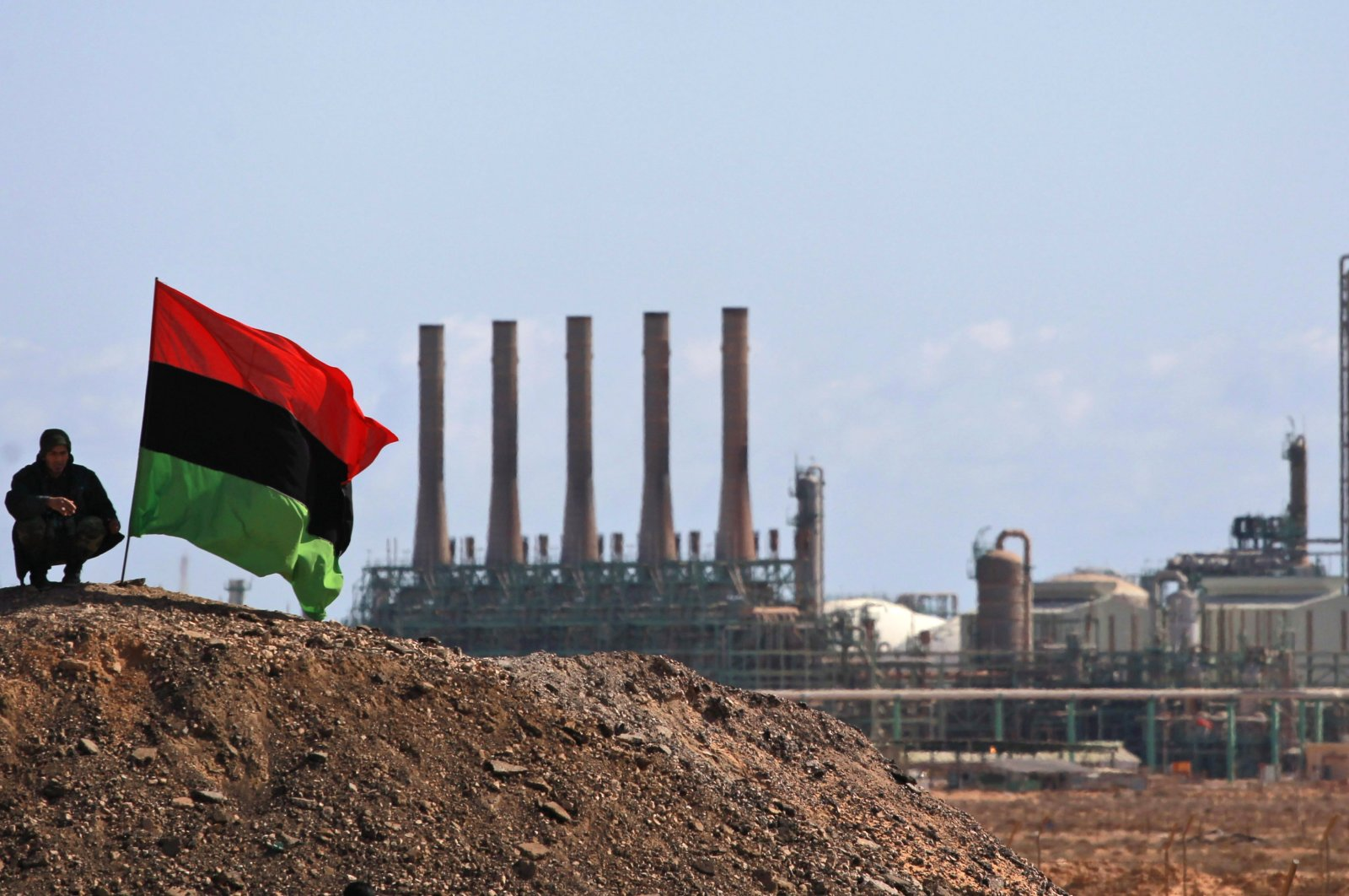A Libyan rebel, part of the forces against Libyan leader Moammar Gadhafi, sits next to a pre-Gadhafi flag as he guards outside the refinery in Ras Lanuf, eastern Libya, on March 7, 2011. (AP File Photo)