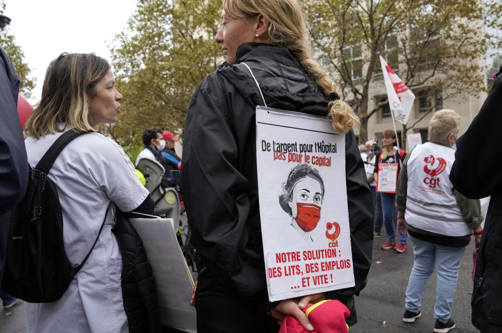 """A medical worker holds a placard reading: """"Money for Hospitals, Not for the Capital. Our Solution: Hospitals beds, Employees... Quickly!"""" during a protest gathering outside the Health Ministry, in Paris, Sept. 14, 2021. (AP Photo)"""