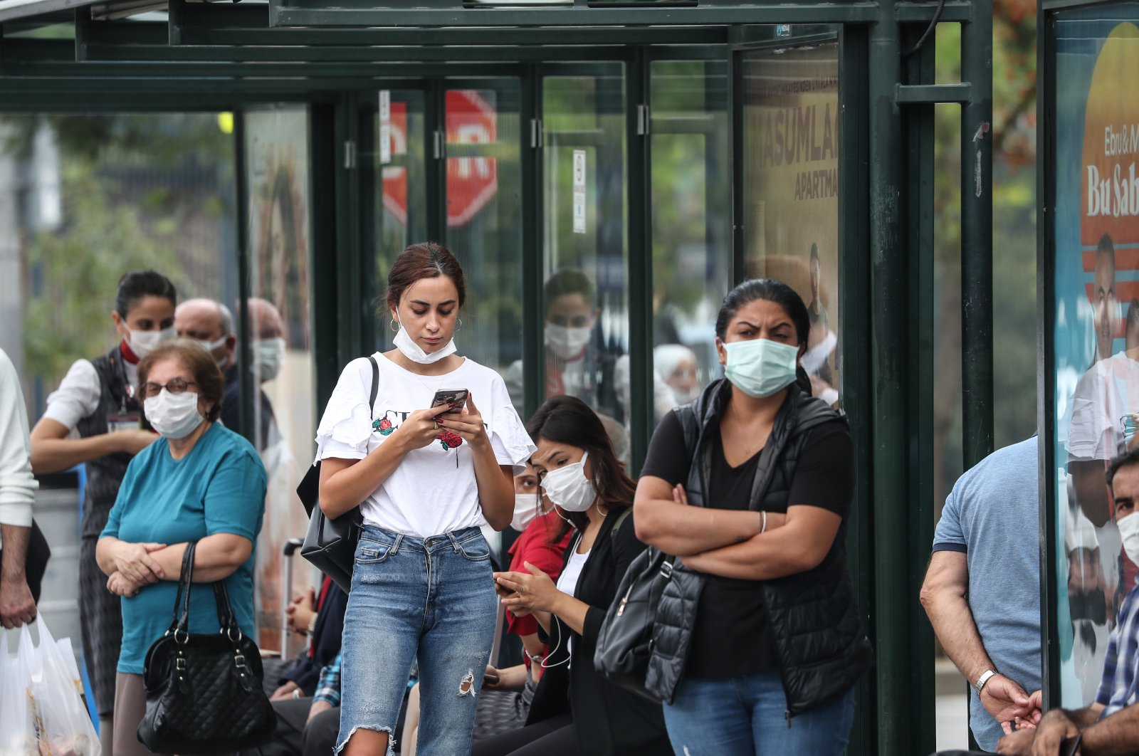 People wearing masks against COVID-19 wait at a bus stop in Istanbul, Turkey, Sept. 15, 2021. (DHA PHOTO)