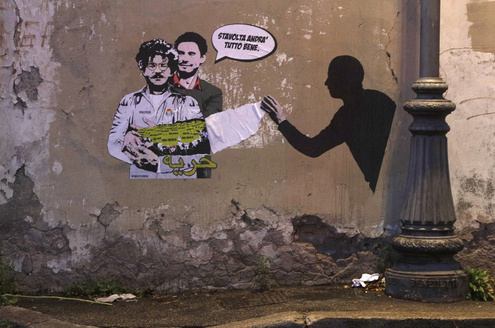 A mural depicting detained Egyptian human rights advocate and student at the University of Bologna in Italy Patrick George Zaki, being hugged from behind by Italian researcher Giulio Regeni, who was murdered in Cairo in 2016, is displayed on a wall in Rome, Italy, Feb. 19, 2020.(AP Photo)