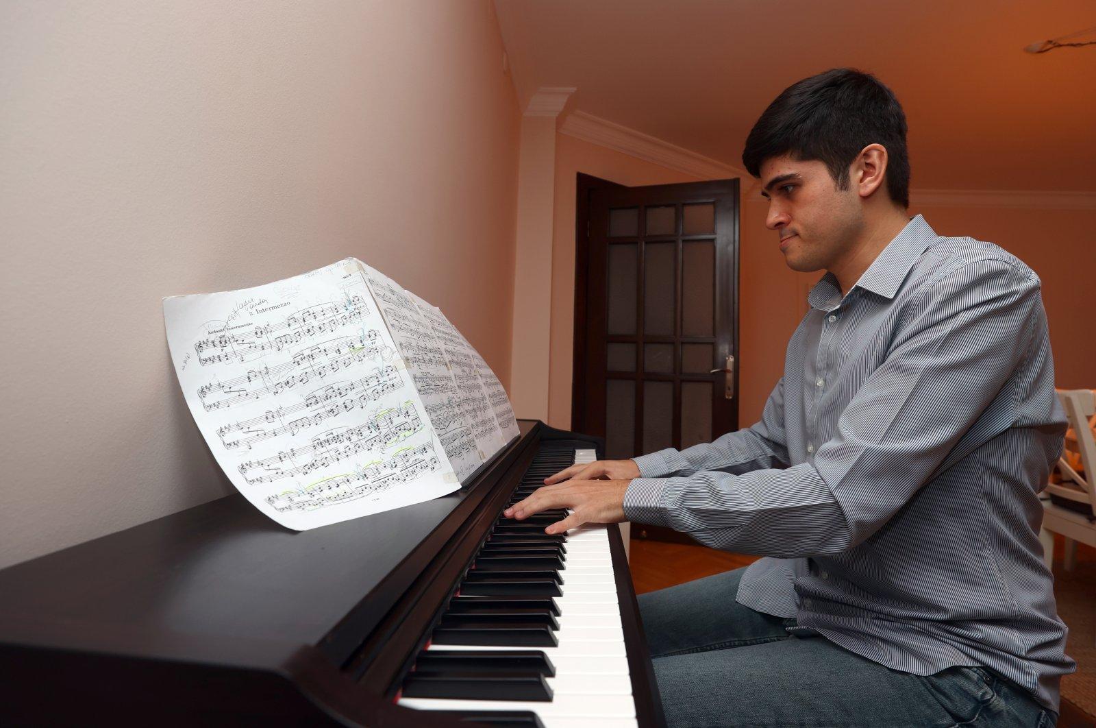 Buğra Çankır plays piano at home, in the capital Ankara, Turkey, Sept. 16, 2021. (AA PHOTO)