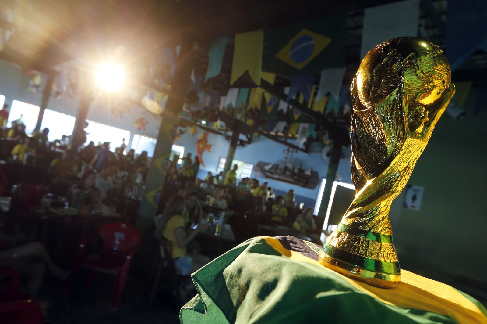 Brazilians watch the opening match of the FIFA World Cup between Brazil and Croatia behind a replica of the trophy in Porto Seguro, Brazil, June 12, 2014. (AP Photo)