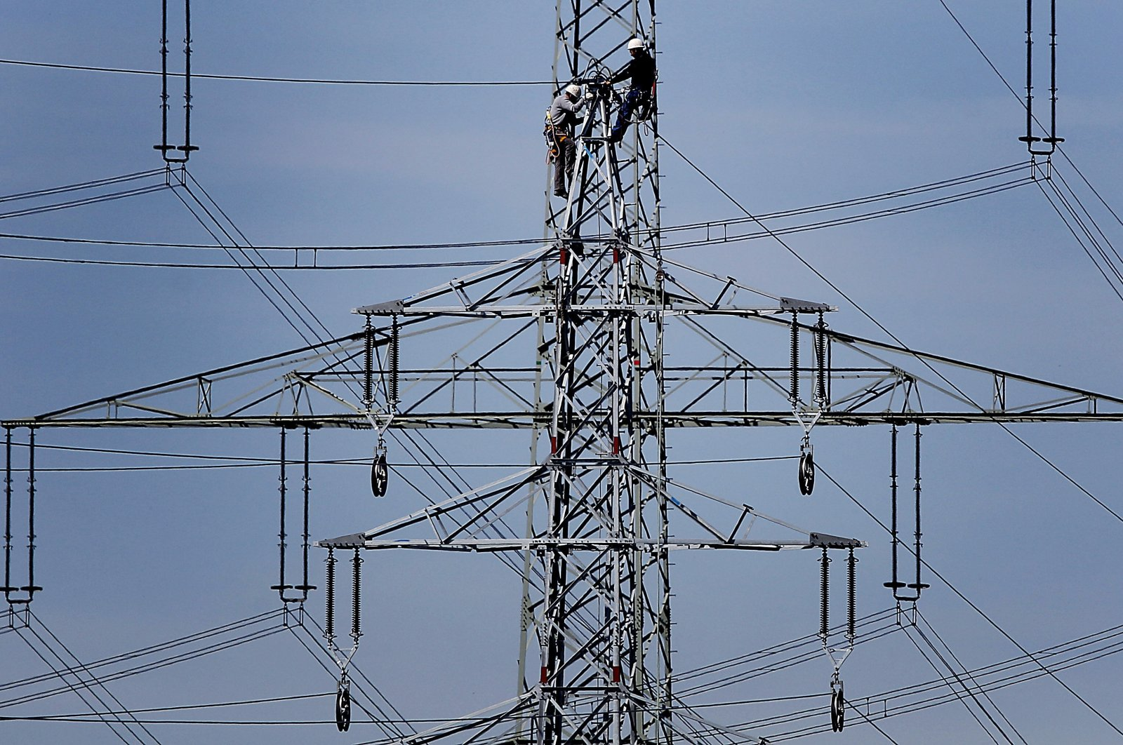 Workers of the German energy company RWE prepare the power supply on a high power pylon in Moers, Germany, April 11, 2011. (AP Photo)