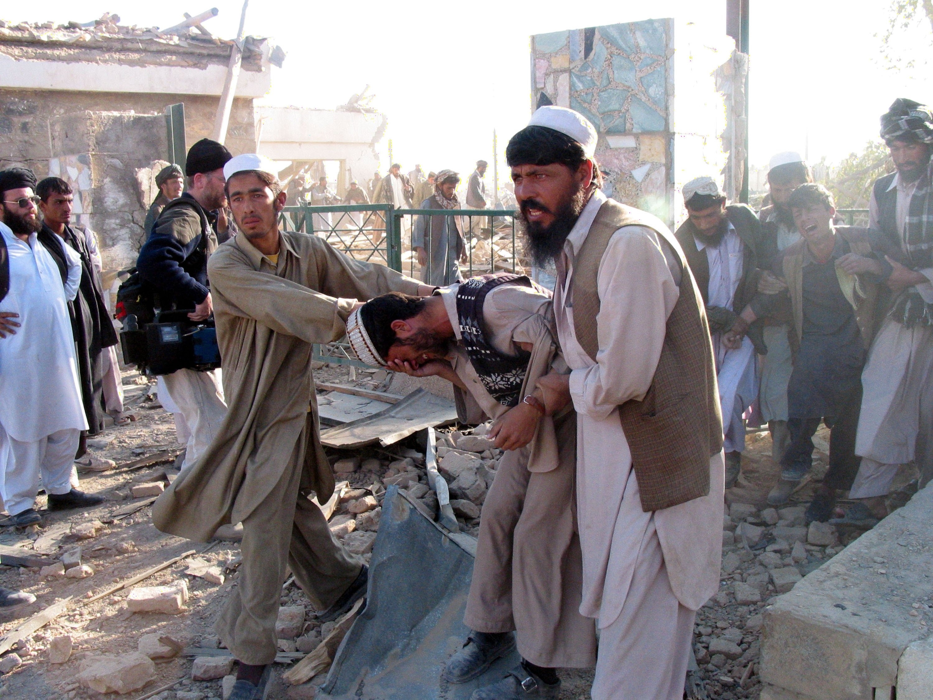 Two men mourn the death of their brother after he was killed when U.S. jets bombed this marble tile factory overnight, in Kabul, Afghanistan, Nov. 11, 2001. (Getty Images)