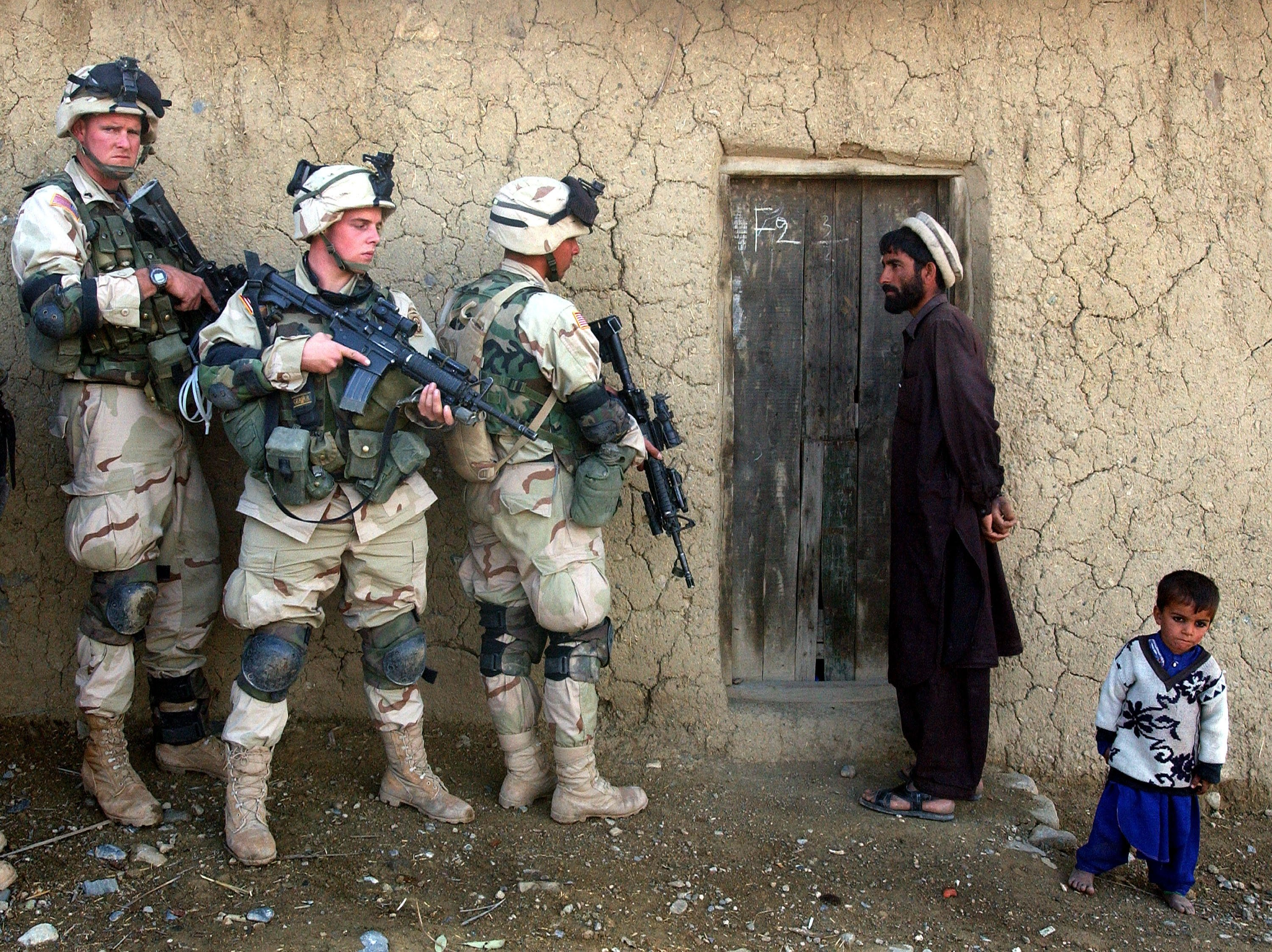An Afghan man and his son watch as soldiers from the U.S. Army 82nd Airborne Division prepare to sweep their home in southeastern Afghanistan, Nov. 7, 2002. (Getty Images)