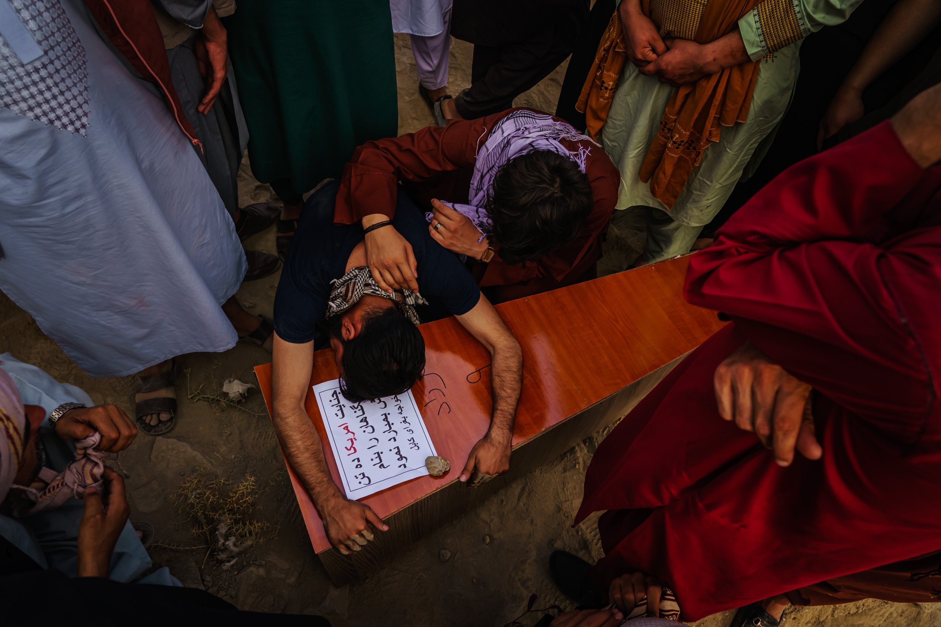A relative weeps over the casket of Farzad, 12, who was killed by U.S. drone airstrikes, Kabul, Afghanistan, Aug. 30, 2021. (Getty Images)