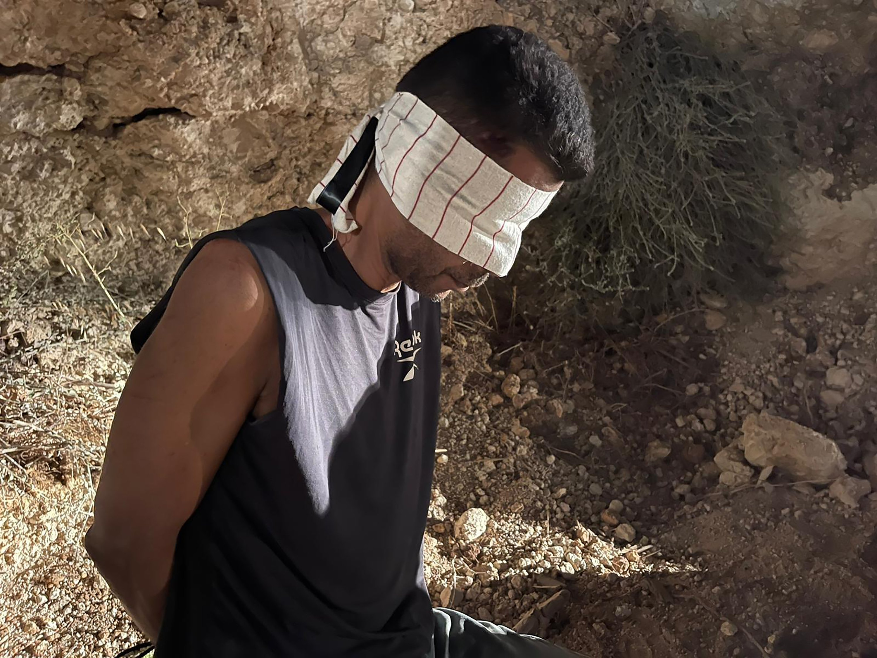 Zakaria Zubeidi, one of the six Palestinians who escaped from a high-security prison earlier this week, is blindfolded and handcuffed after being recaptured in the town of Umm al-Ghanam, northern Israel, Sept. 11, 2021. (AP Photo)