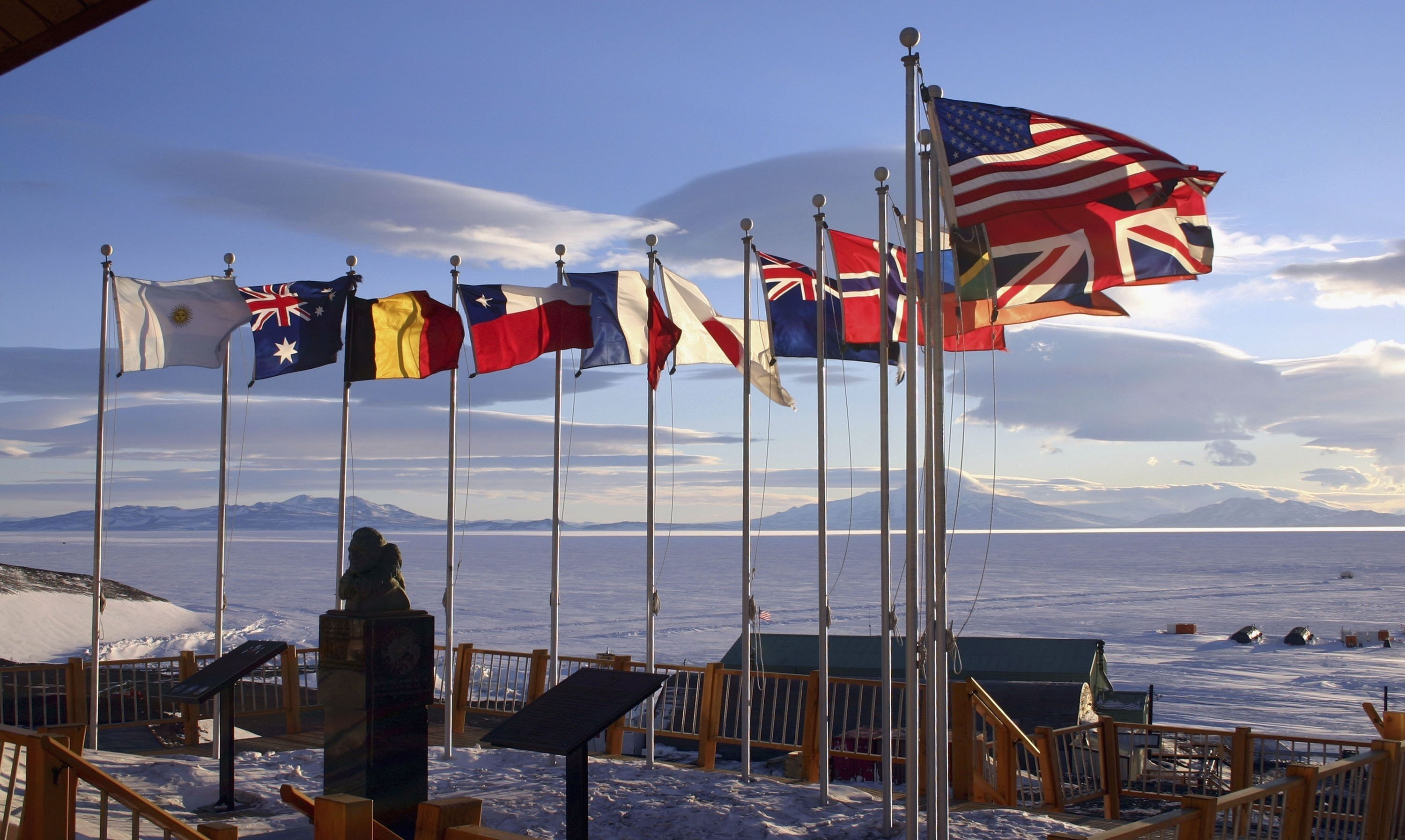 Flags of the original 12 signatory nations of the Antarctic Treaty fly next to a bust of Admiral Richard Byrd at McMurdo Station on October 21, 2005, in Antarctica. (Getty Images)