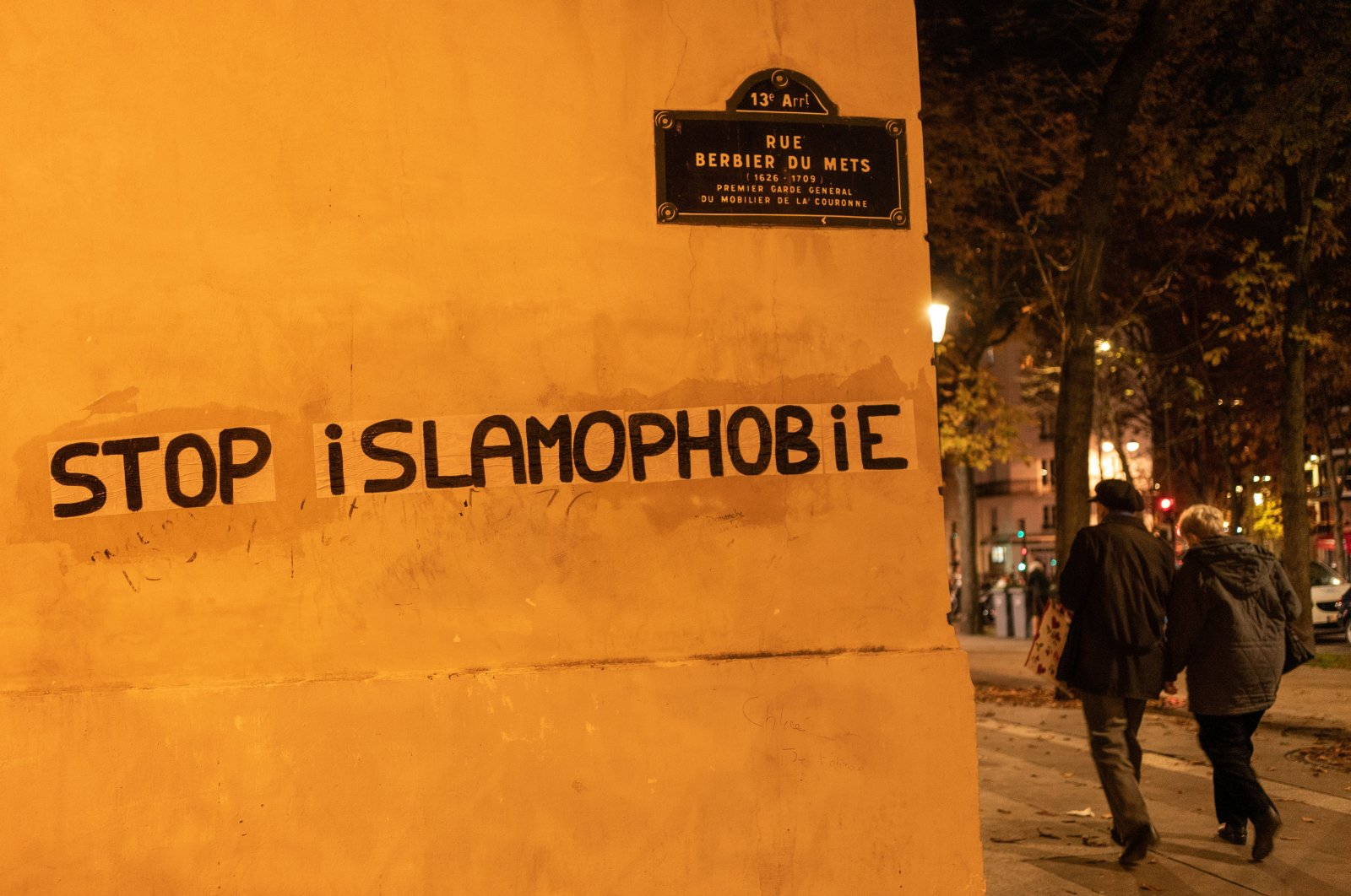 """People walk past graffiti that reads """"Stop Islamophobia,"""" in Paris, France, Oct. 26, 2020. (Getty Images)"""